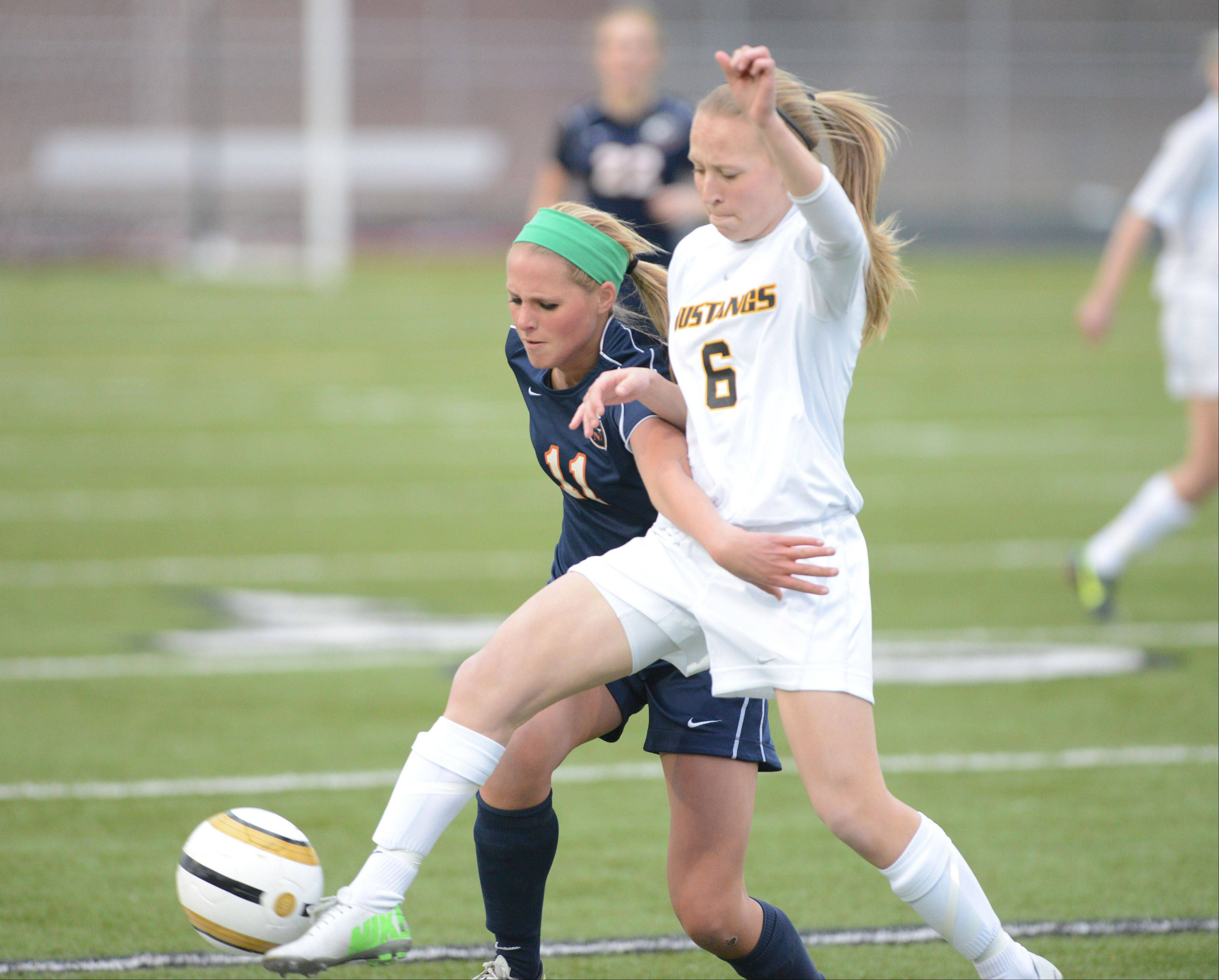 Sarah Feder, left, of Naperville North and Alena Sidwell of Metea Valley dual for the ball during the Naperville North at Metea Valley girls soccer game Tuesday.