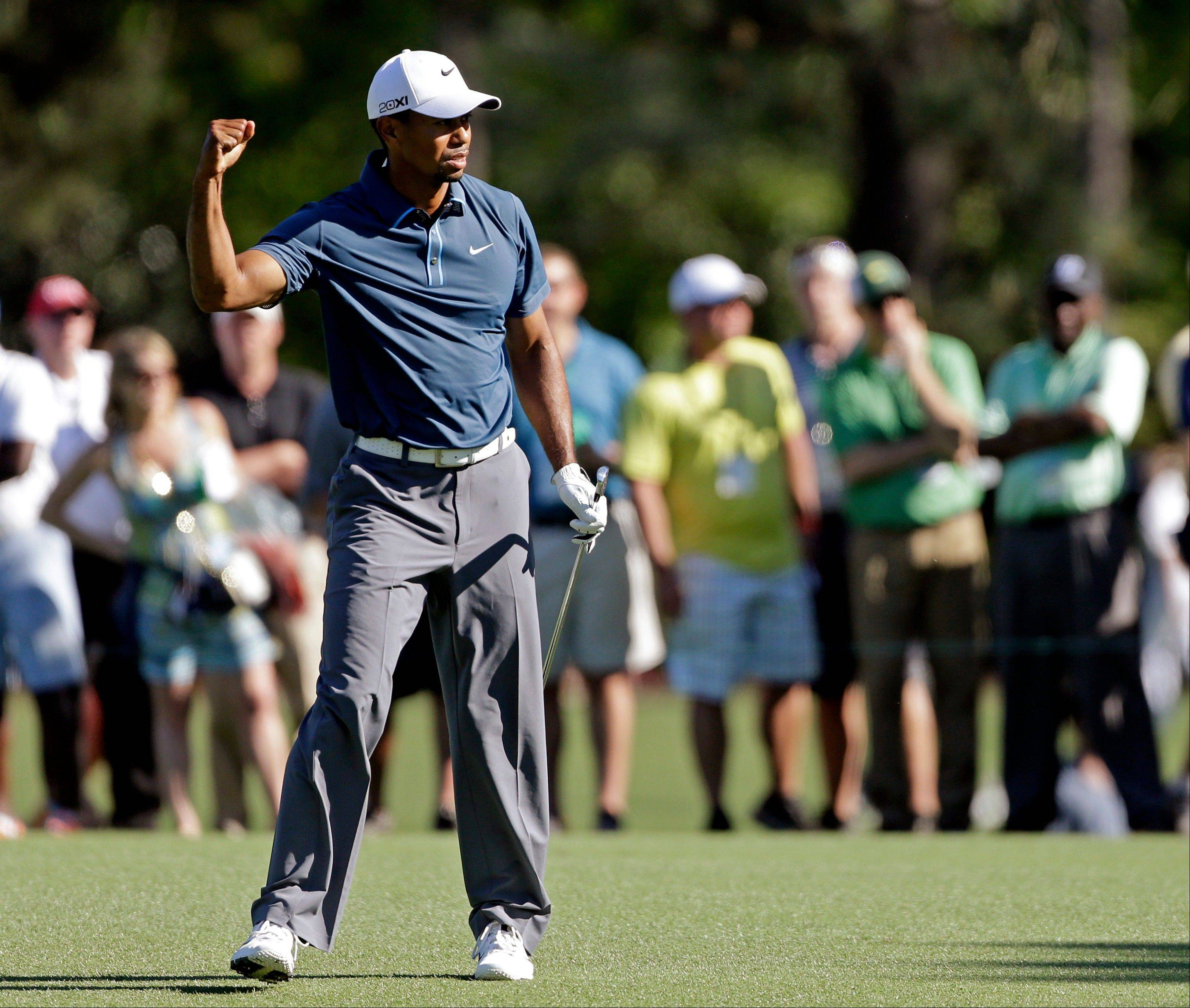 Tiger Woods reacts to his approach shot to the 15th green during the third round of the Masters on Saturday. Later he was assessed a two-stroke penalty by the Masters committee, which did not disqualify him.