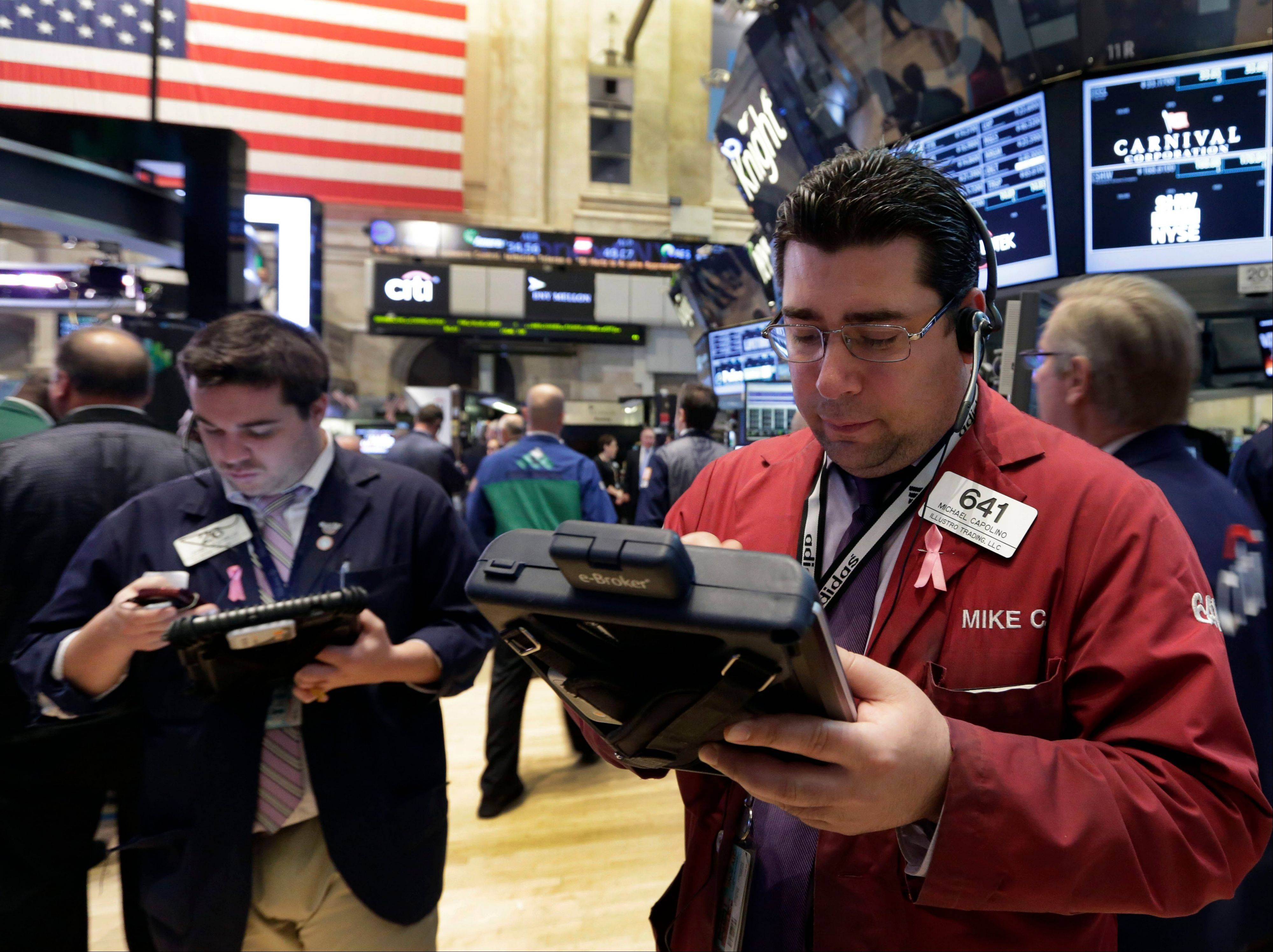 Michael Capolino, right, works with fellow traders on the floor of the New York Stock Exchange Tuesday, April 16, 2013. Stocks are sharply higher in early trading, a day after the market's worst drop this year, as the government reported a surge in home construction last month.