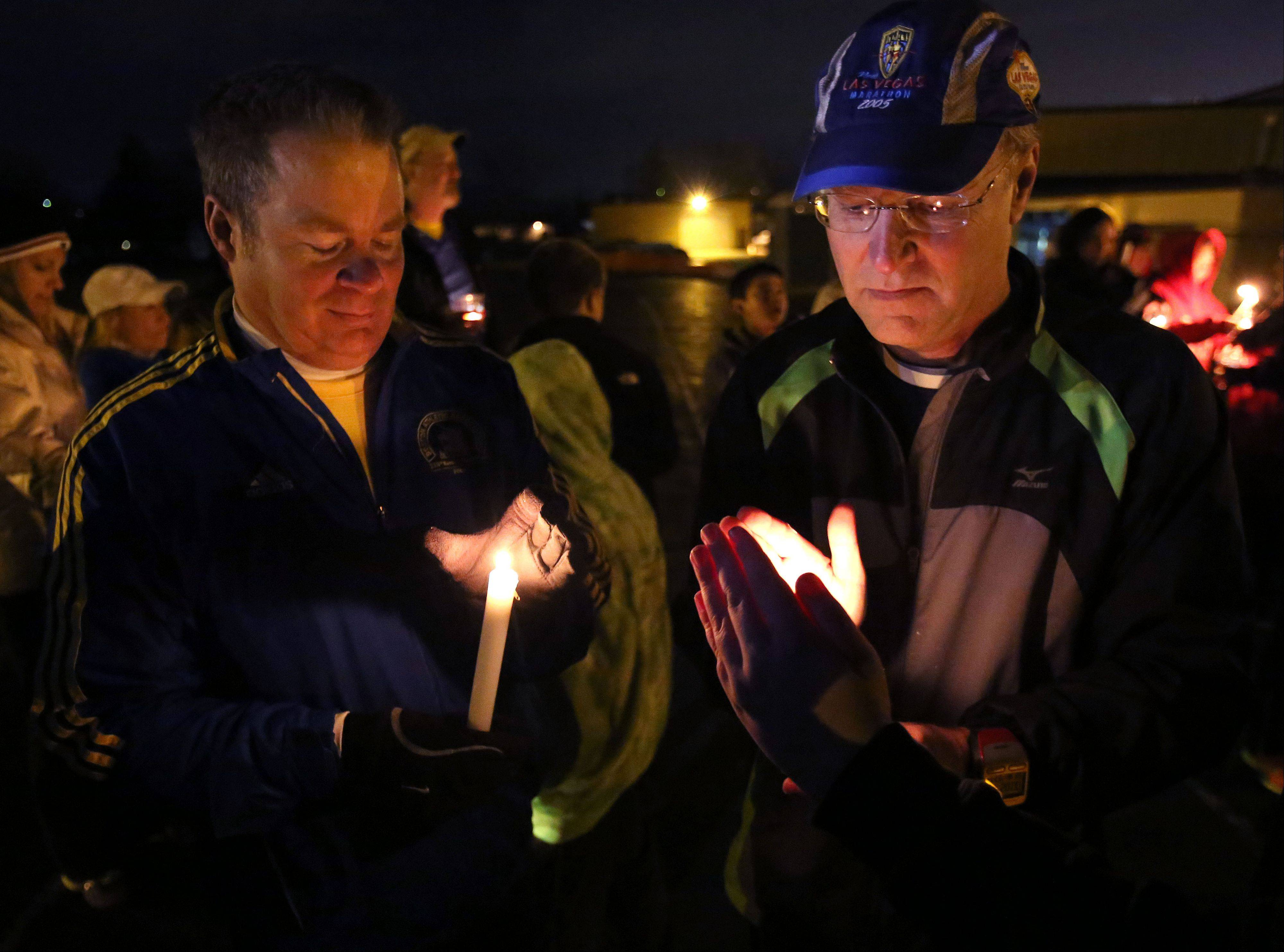 Don Gill and Craig Wiemer, both of Palatine, light candles as members of the Hoffman Estates, Inverness and Palatine, or HIP Athletic Association hold a memorial run on the track at the old Palatine High School for the victims of the Boston Marathon bombings.