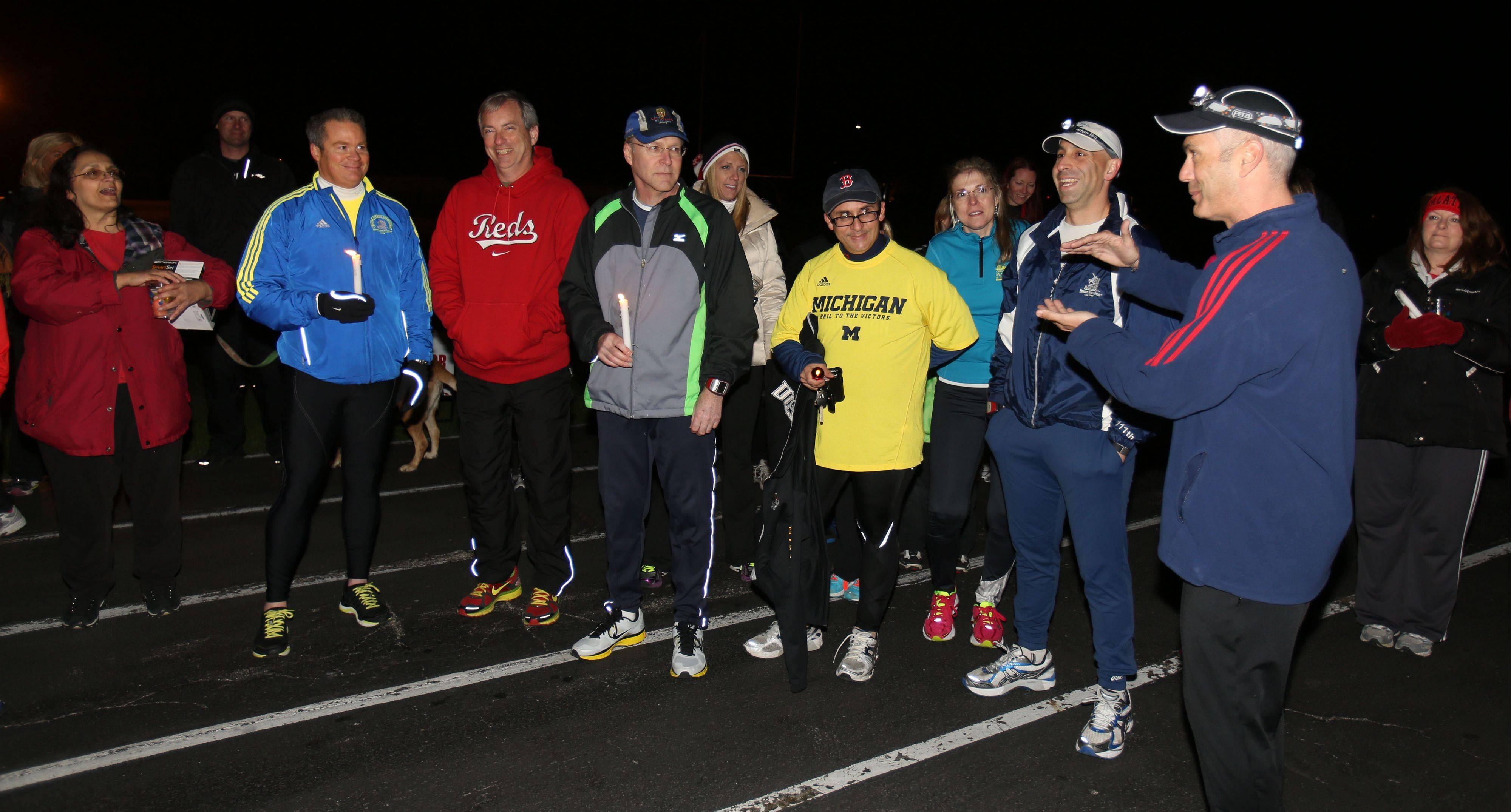 Members of the Hoffman Estates, Inverness and Palatine, or HIP, Athletic Association gather as they hold a memorial run on the track at the old Palatine High School for the victims of the Boston Marathon bombings.