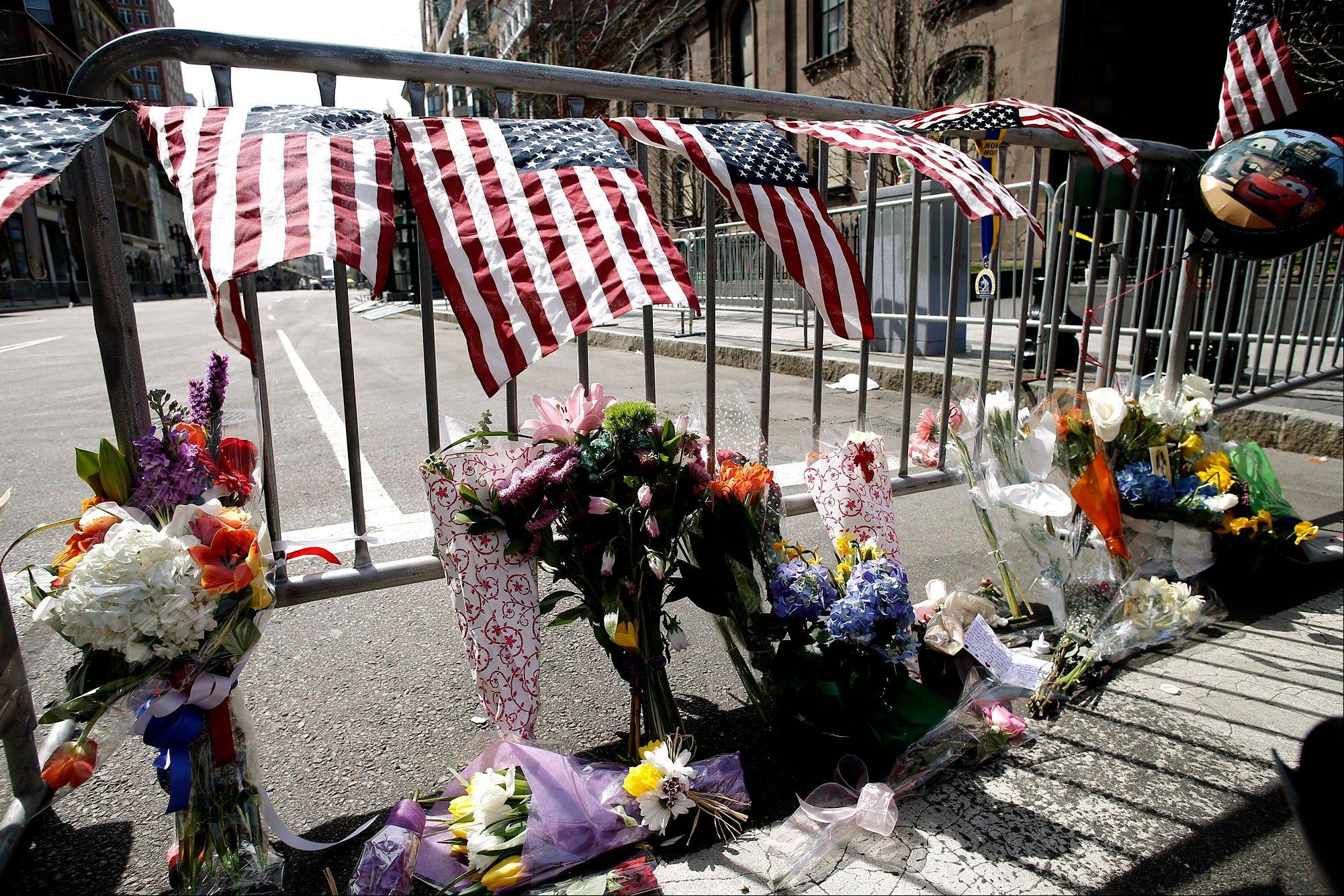 Flowers sit at a police barrier Tuesday near the finish line of the Boston Marathon in Boston. The bombs that ripped through the crowd at the Bosto