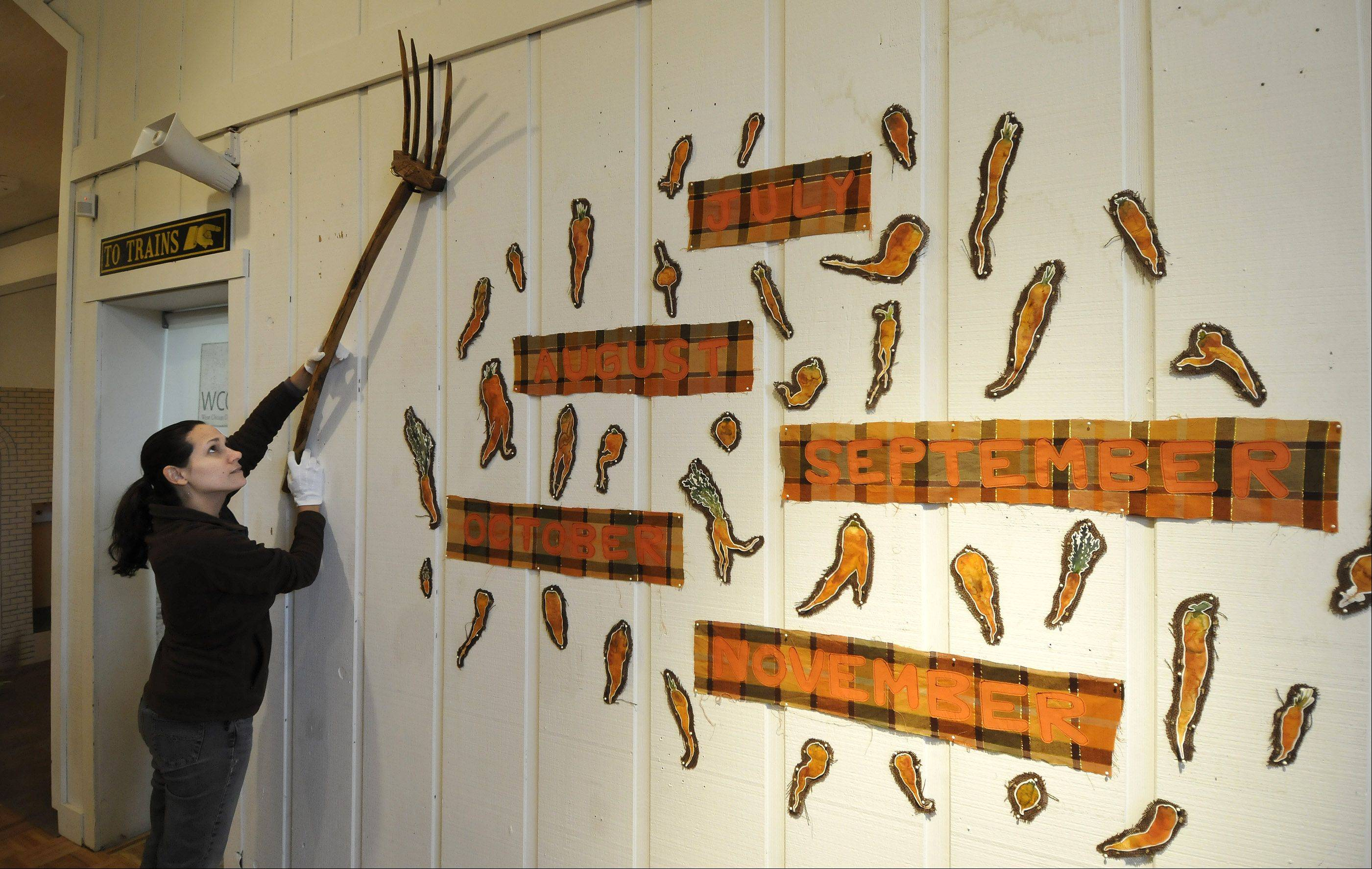West Chicago City Museum Director/Curator Sara Phalen positions an old-fashioned rake on a wall hanging by Chicago artist Kim Guare showing the months carrots can be grown in the Midwest.