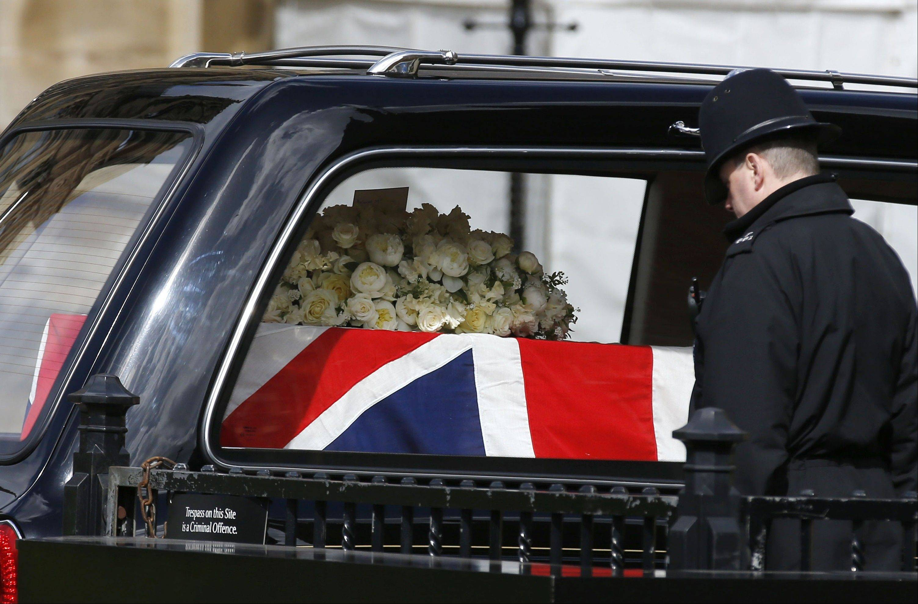A British police officer bows his head as the Union flag draped coffin holding the body of former British Prime Minister Margaret Thatcher arrives in a hearse at the Houses of Parliament in London to rest overnight before her funeral the next day, Tuesday, April 16, 2013. About 100 colleagues and senior politicians will attend a private service in Parliament's chapel of St. Mary Undercroft later Tuesday. The Iron Lady, who transformed Britain during her 11-year tenure, died April 8, aged 87.