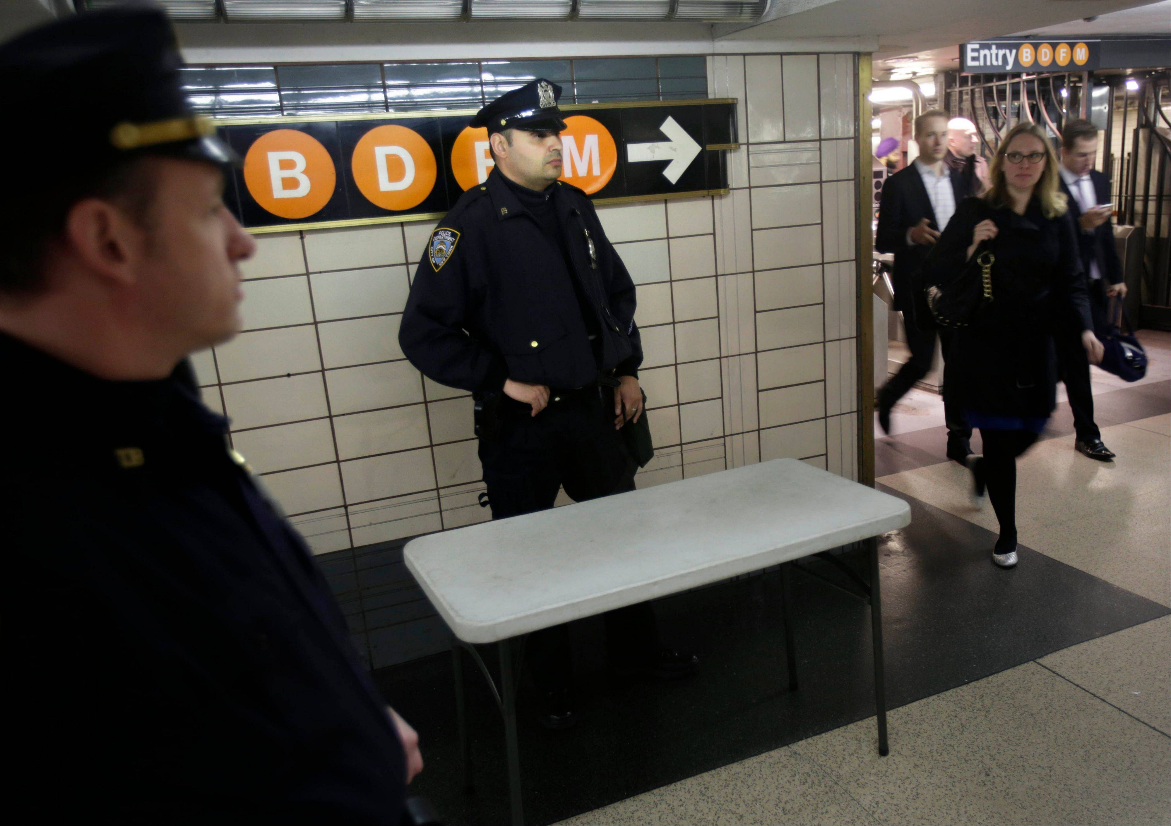 Police officers keep an eye on commuters in a subway station in New York, Tuesday, April 16, 2013. Police armed with rifles and extra patrol cars were stationed around the city Tuesday as New York remained in a heightened state of alert until more is known about the bombings at the Boston Marathon.