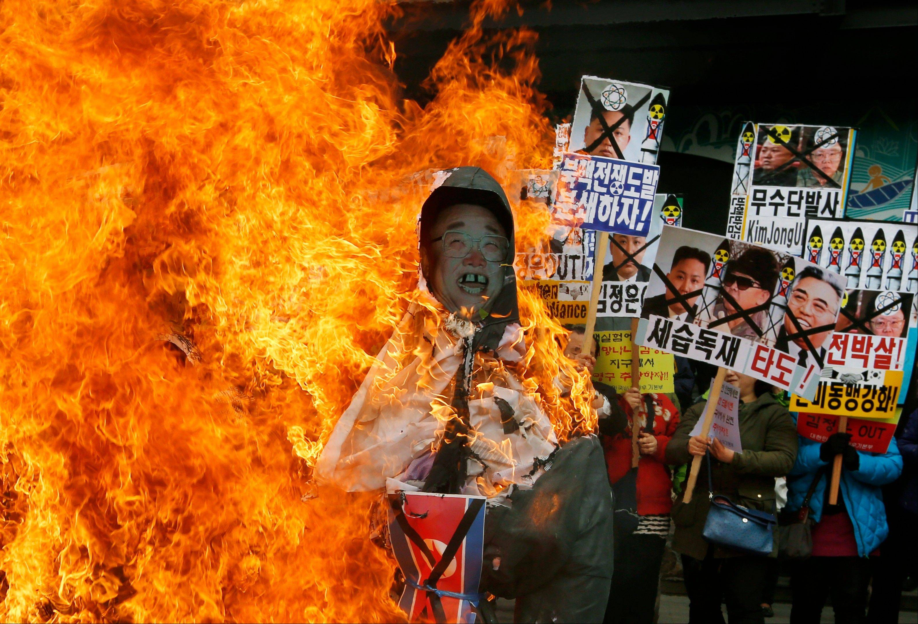 "South Korean protesters burn effigies of North Korean leader Kim Jong-Un, and late leaders Kim Jong Il and Kim Il Sung at an anti-North Korea protest on the birthday of Kim Il Sung in Seoul, South Korea. North Korea lashed out anew Tuesday, April 16, 2013 at South Korea over the small public protest, saying it would not hold talks with its southern neighbor unless it apologized for anti-North Korean actions ""big and small."" The sign at center showing images of the Kim family reads ""Throw Them Out."""