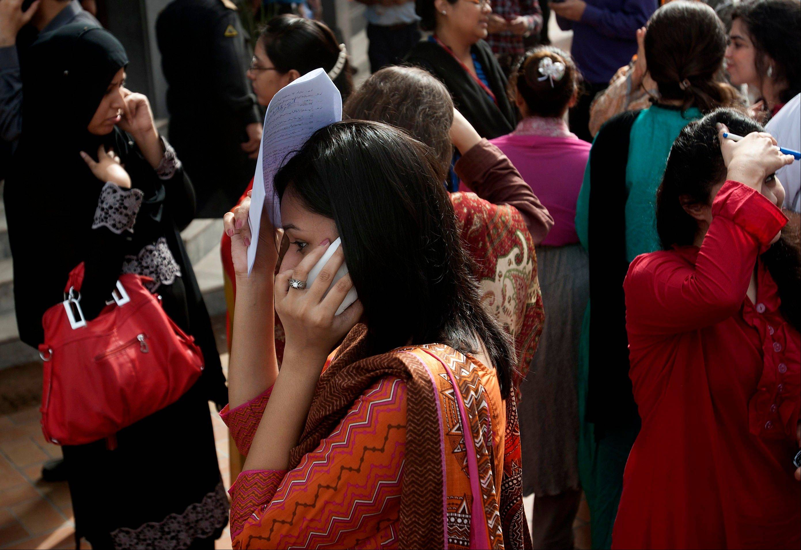 People evacuate buildings and call their relatives after a tremor of an earthquake was felt in Karachi, Pakistan, Tuesday, April 16, 2013. A major earthquake described as the strongest to hit Iran in more than half a century flatted homes and offices Tuesday near Iran's border with Pakistan, killing at least tens of people in the sparsely populated region and swaying buildings as far away as New Delhi and the skyscrapers in Dubai and Bahrain.