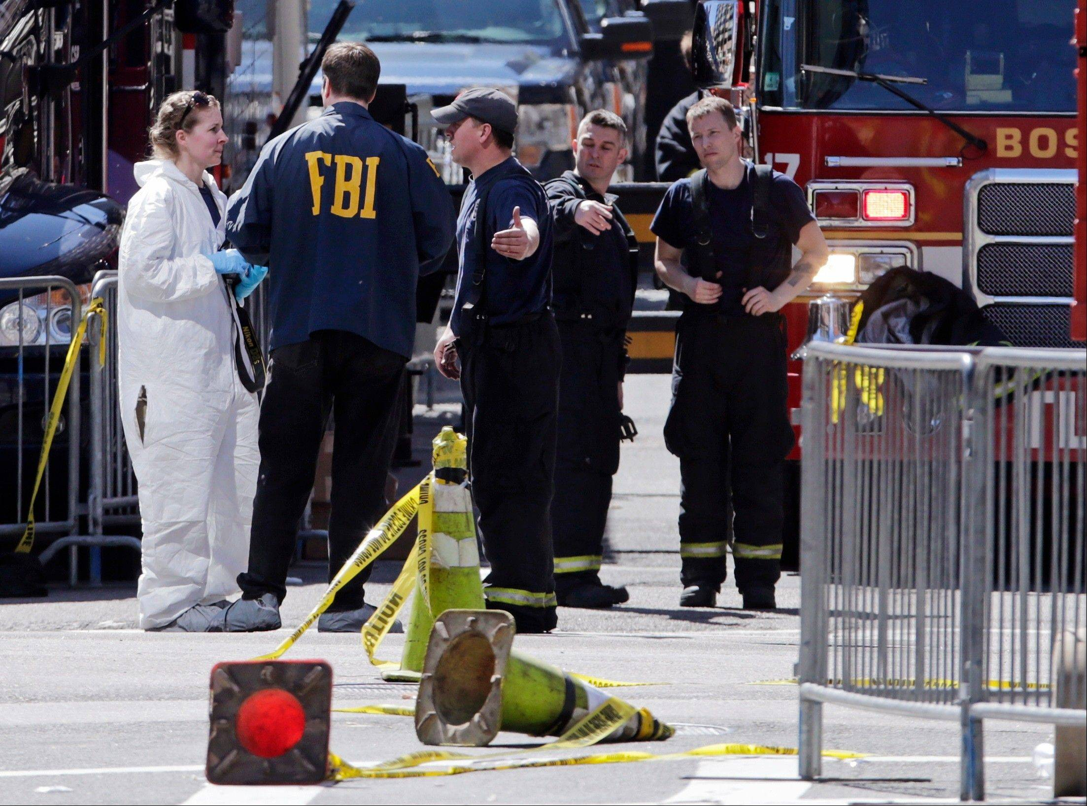 Boston firefighters, right, talk Tuesday with FBI agents and a crime scene photographer at the scene of Monday's Boston Marathon explosions, which killed at least three and injured more than 140, in Boston. The bombs that blew up seconds apart near the finish line left the streets spattered with blood and glass, and gaping questions of who chose to attack at the Boston Marathon and why.