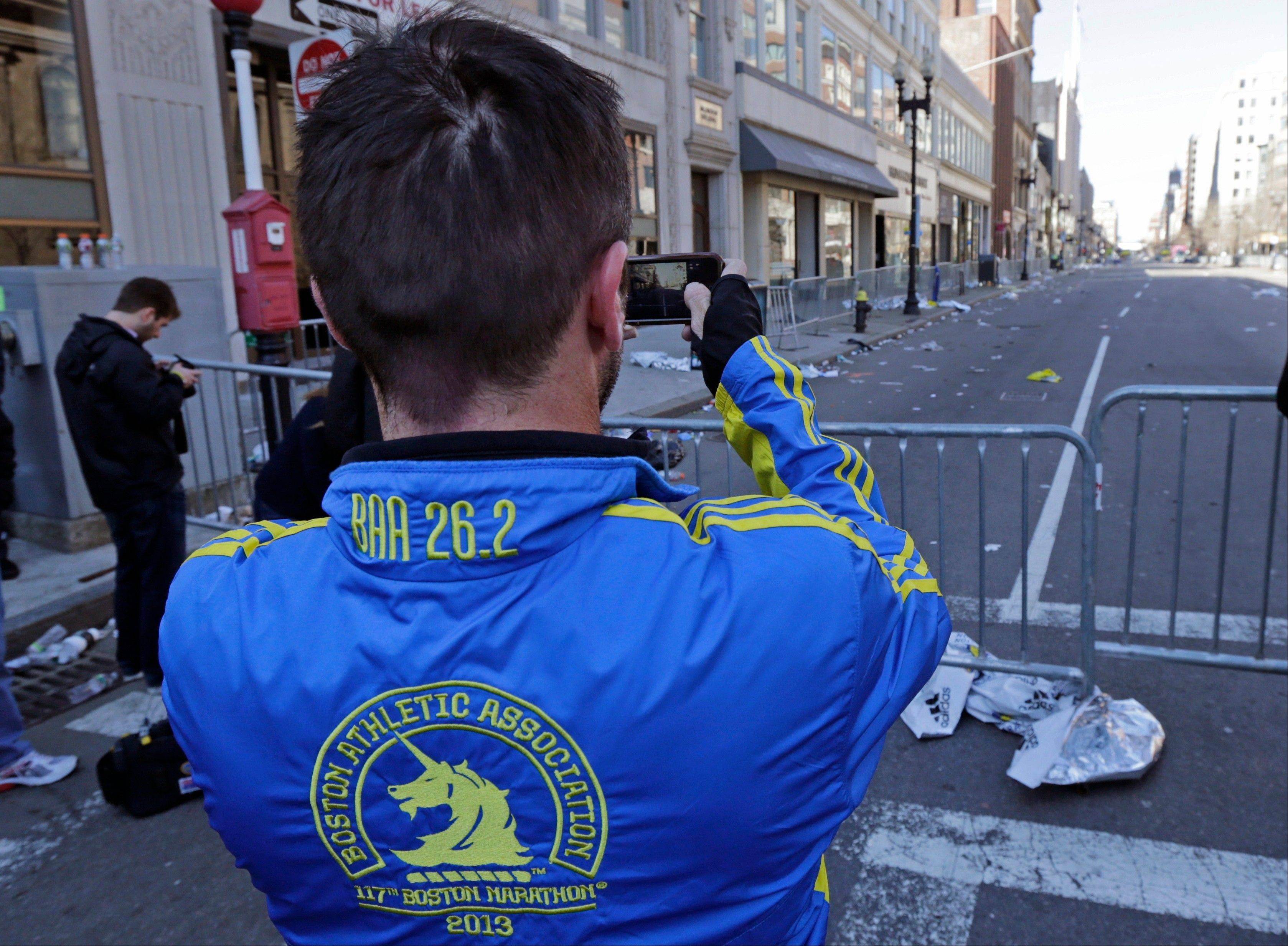 Paul McRae, a native of New Zealand now living in Jacksonville, takes a photograph Tuesday of an empty Boylston Avenue near the Boston Marathon finish line. Police and federal agents appealed to the public Tuesday for amateur video and photos that might yield clues to the Boston Marathon bombing.