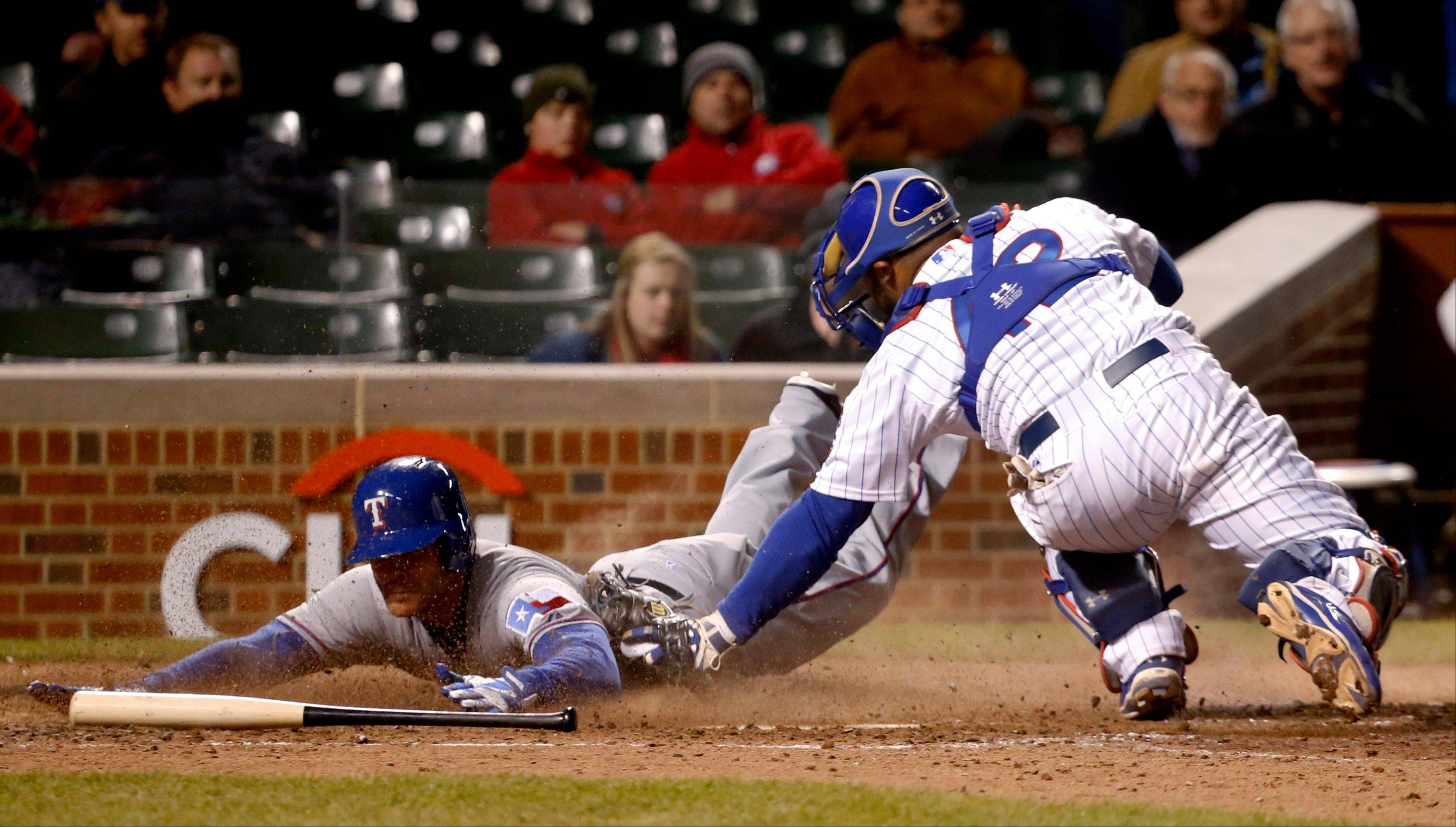 Chicago Cubs catcher Welington Castillo, right, tags out Texas Rangers' Craig Gentry at home on a throw from first baseman Anthony Rizzo during the ninth inning of a interleague baseball game, Tuesday, April 16 2013, in Chicago.
