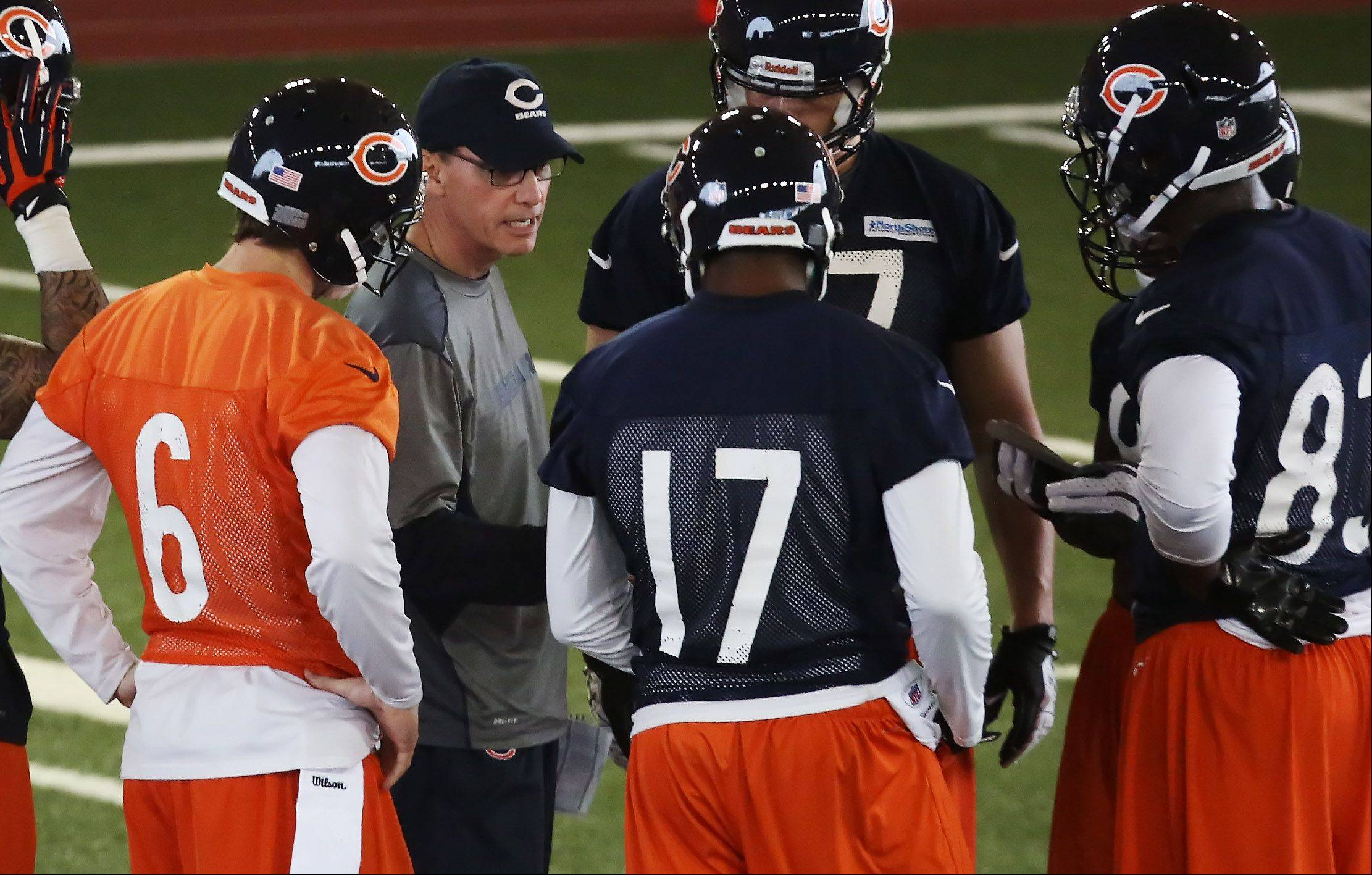 Coach Marc Trestman talks to quarterback Jay Cutler, left, and his receivers during the first day of the Bears minicamp Tuesday.