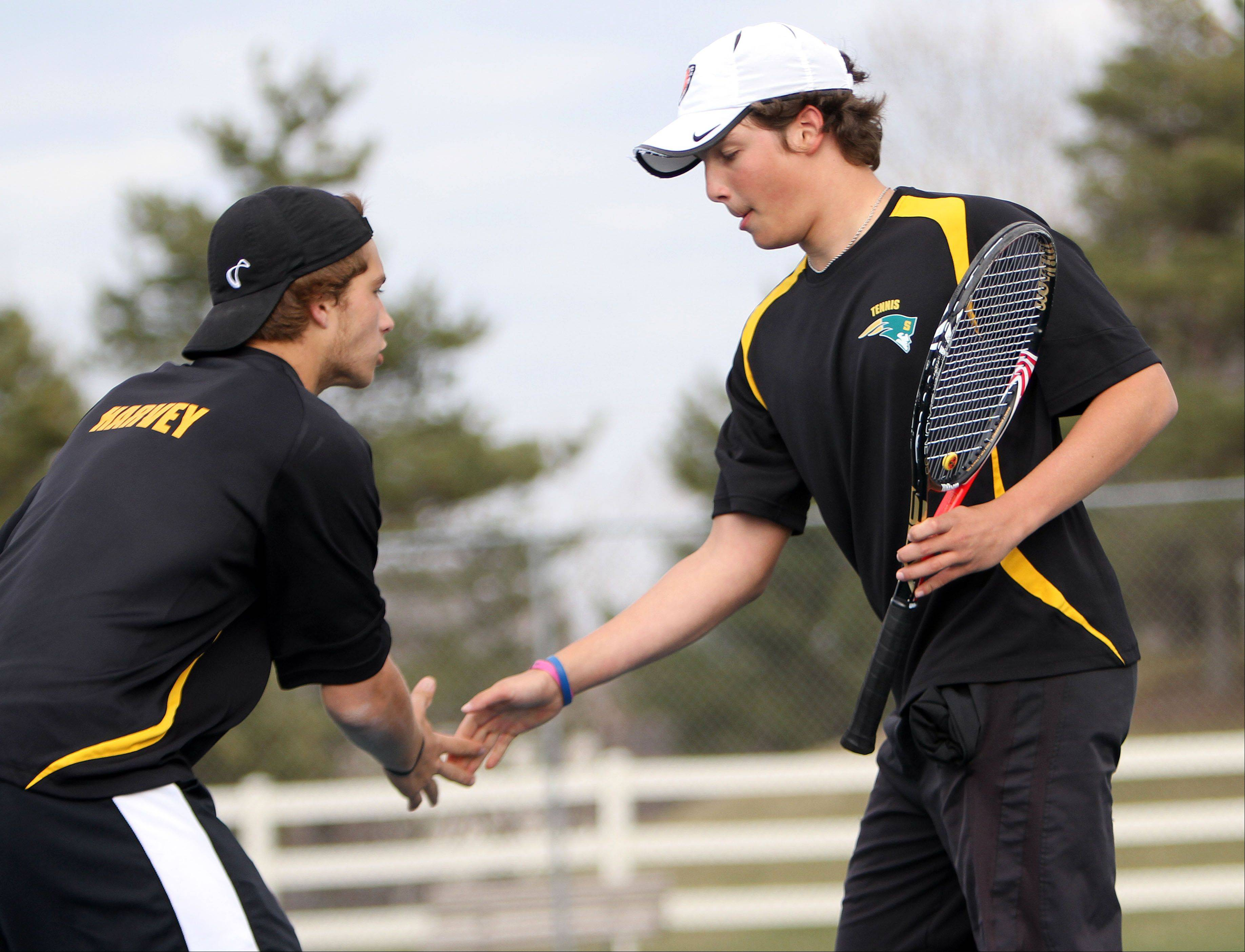 Stevenon's doubles partners Colin Harvey, left and Andrew Komarov celebrate after winning a point during their match against Warren on Tuesday in Gurnee.