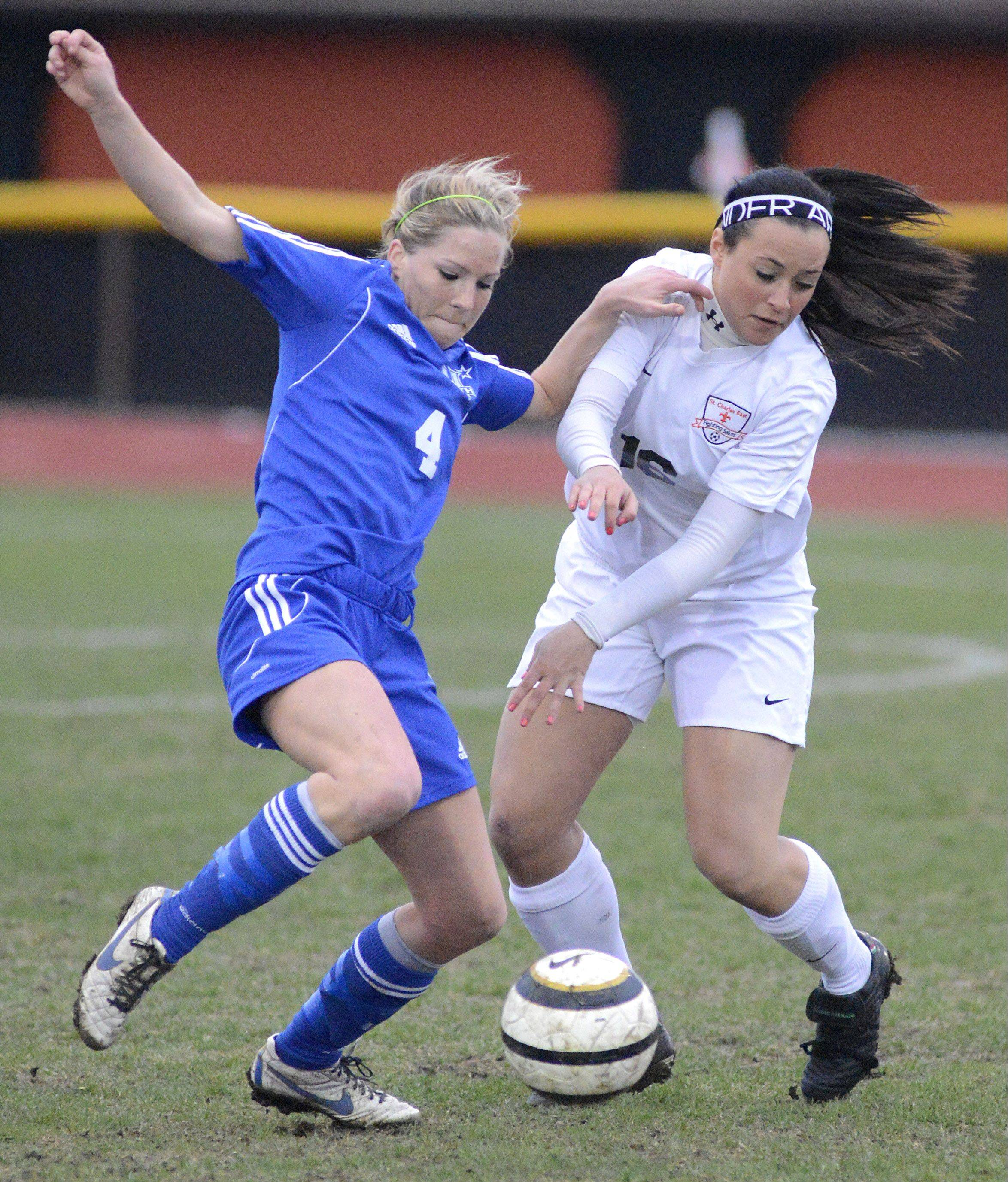 St. Charles North's Jenny Barr and St. Charles East's Hannah Rawson fight for possession of the ball.