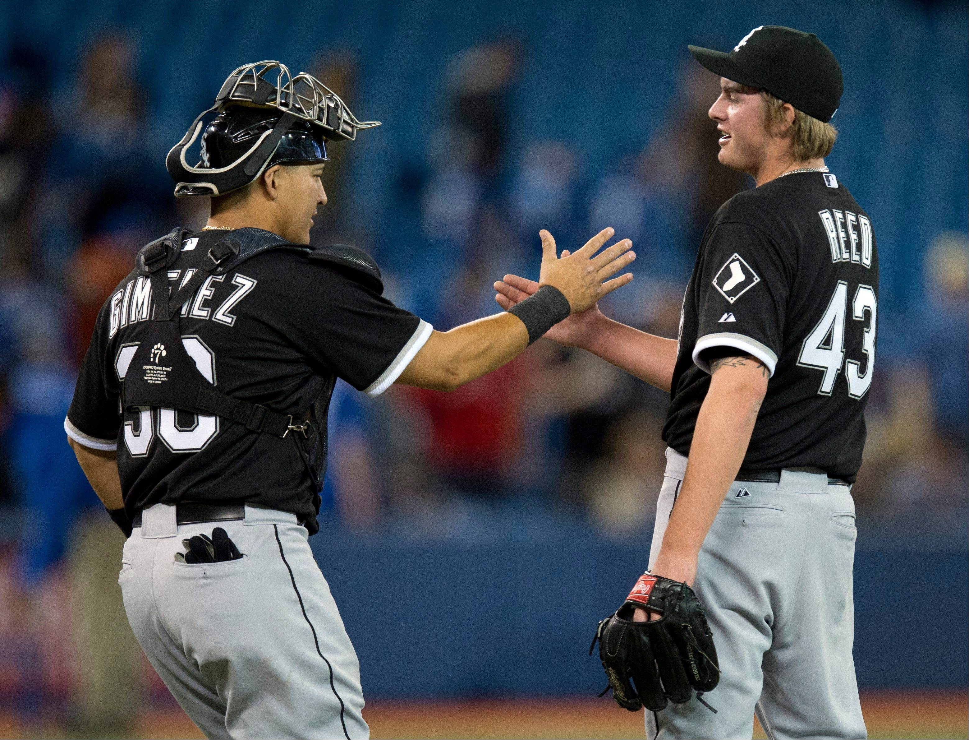 White Sox catcher Hector Gimenez congratulates pitcher Addison Reed after defeating the Blue Jays Tuesday night in Toronto.