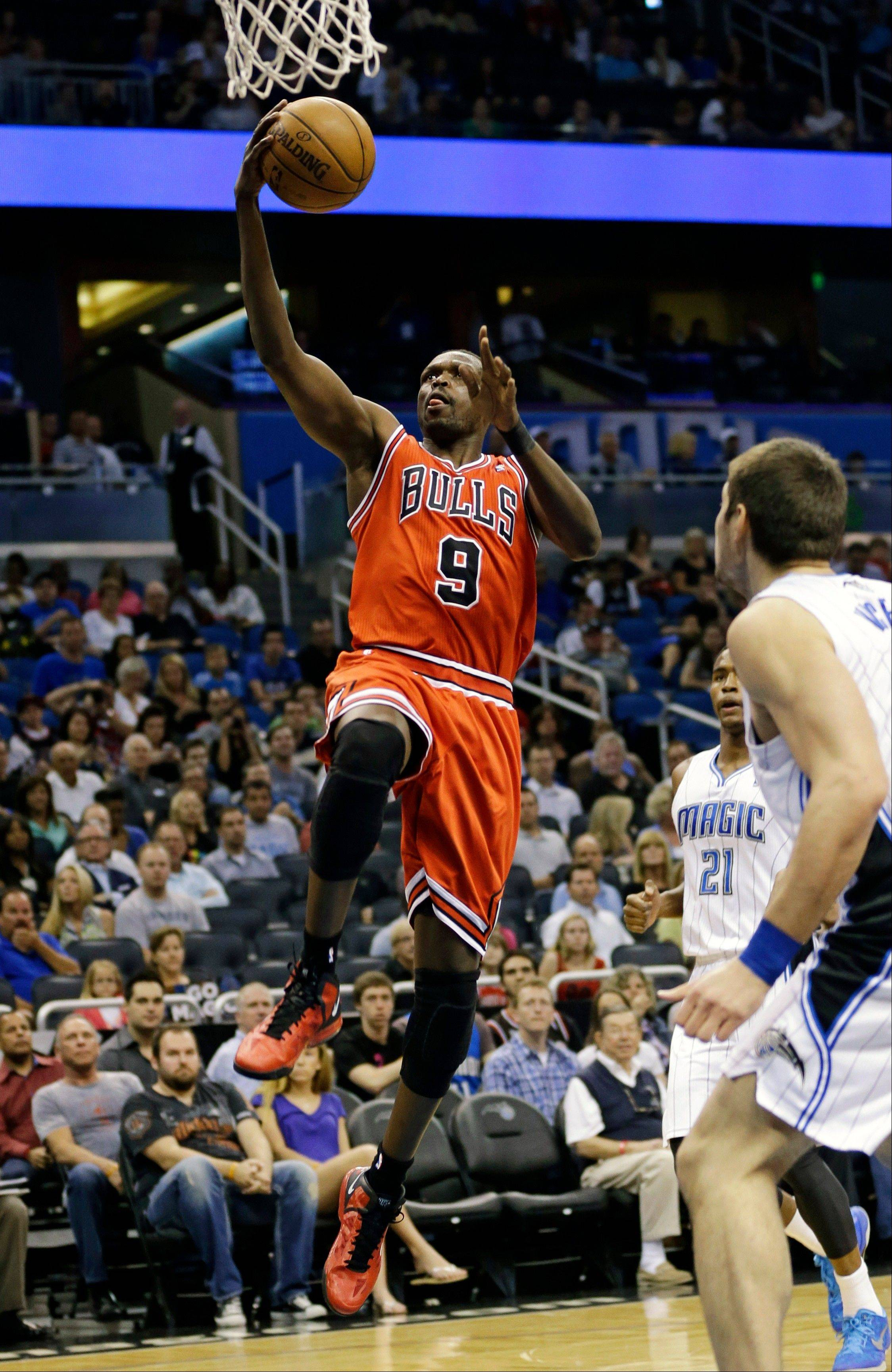 Chicago Bulls' Luol Deng (9) drives to the basket past Orlando Magic's Maurice Harkless (21) and Nikola Vucevic, right, of Montenegro, on Monday night in Orlando, Fla.