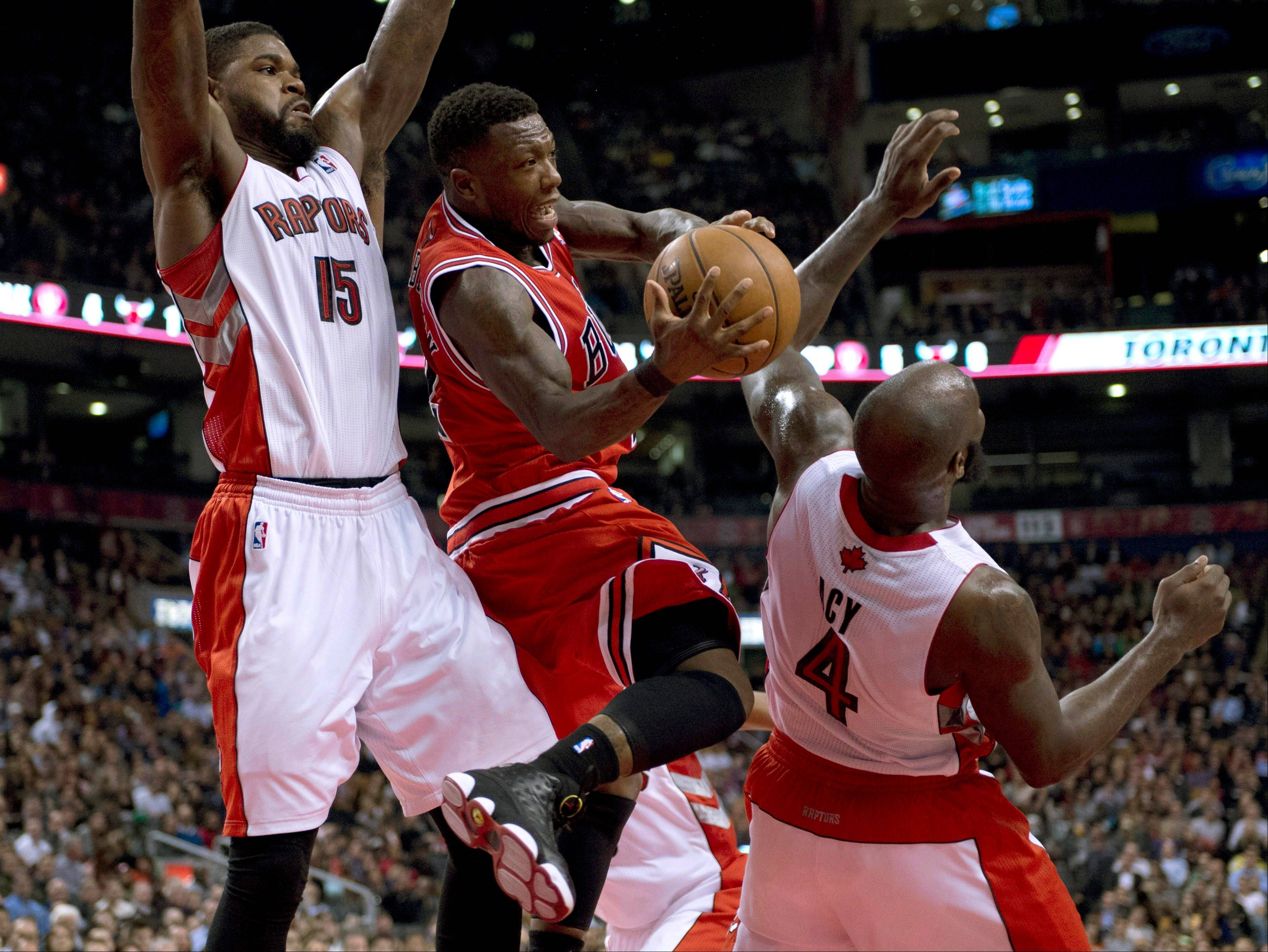 Chicago Bulls guard Nate Robinson, center, passes off the ball as he runs into Toronto Raptors forwards Amir Johnson, left, and Quincy Acy last Friday in Toronto.