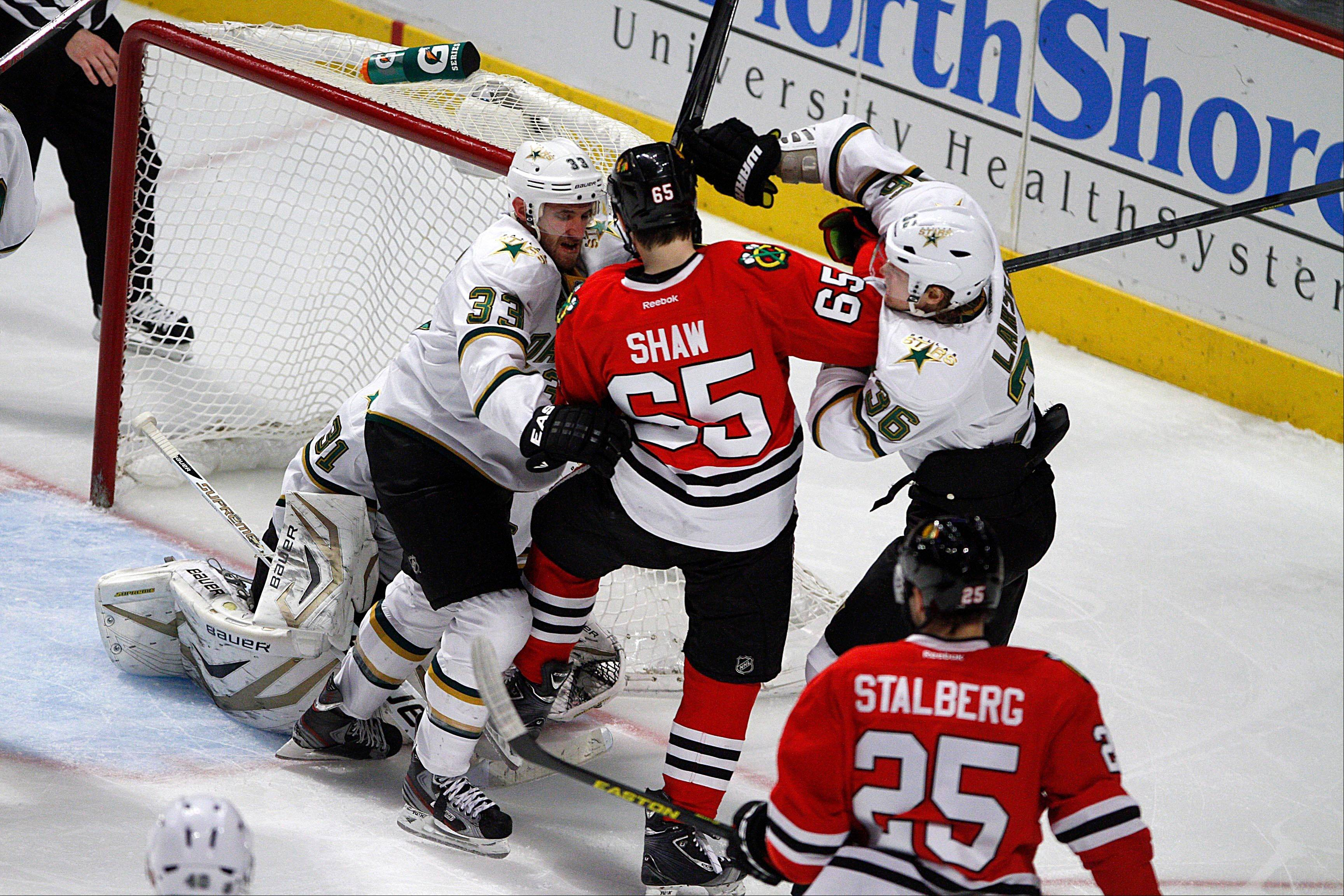 Dallas Stars' Alex Goligoski (33) and Philip Larsen (36) pull the Blackhawks' Andrew Shaw away from their goalie during third-period action as the Blackhawks defeated the Stars 5-2 Monday.
