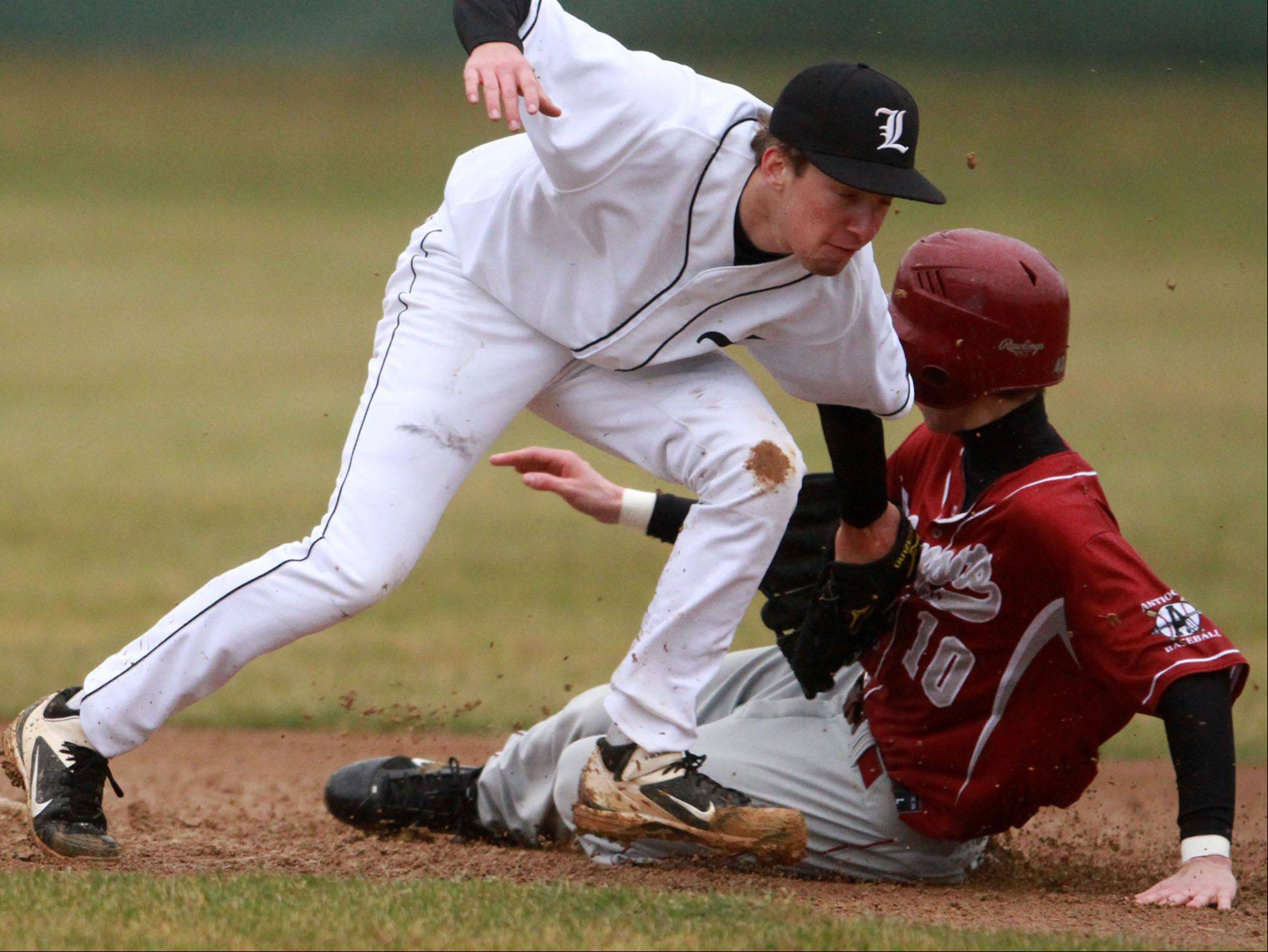 Antioch's Mitch Everett slides into second base as Libertyville shortstop Jimmy Govern misses the tag Friday in Libertyville.