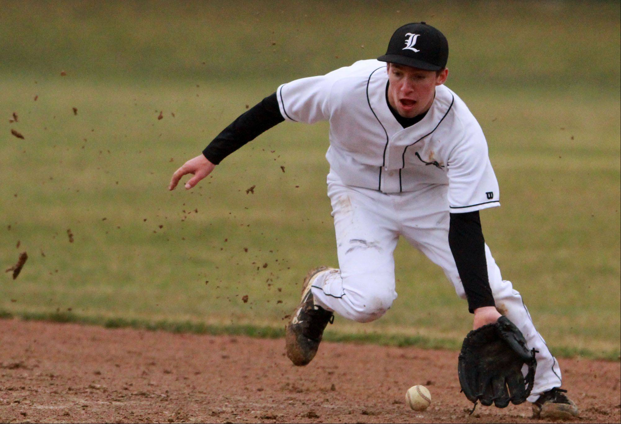 Libertyville shortstop Jimmy Govern scoops up a grounder against Antioch Friday in Libertyville.