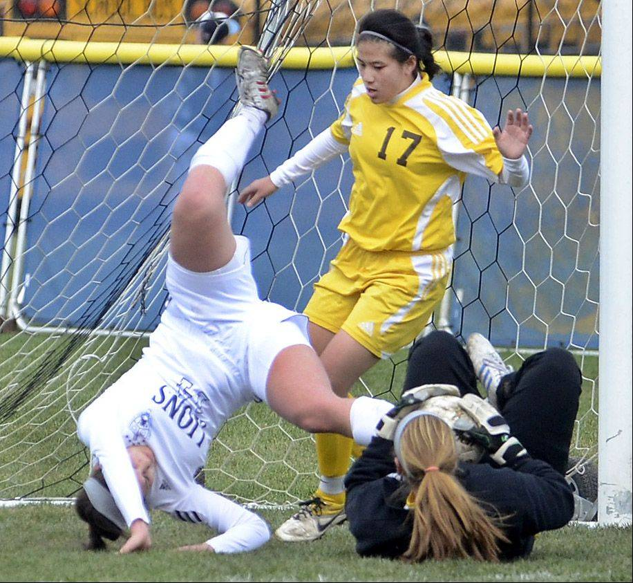 St. Viator's Michelle Trovato gets tangled-up with Carmel goalkeeper Jenna Bauer and Emily Helle during Saturday's soccer game.