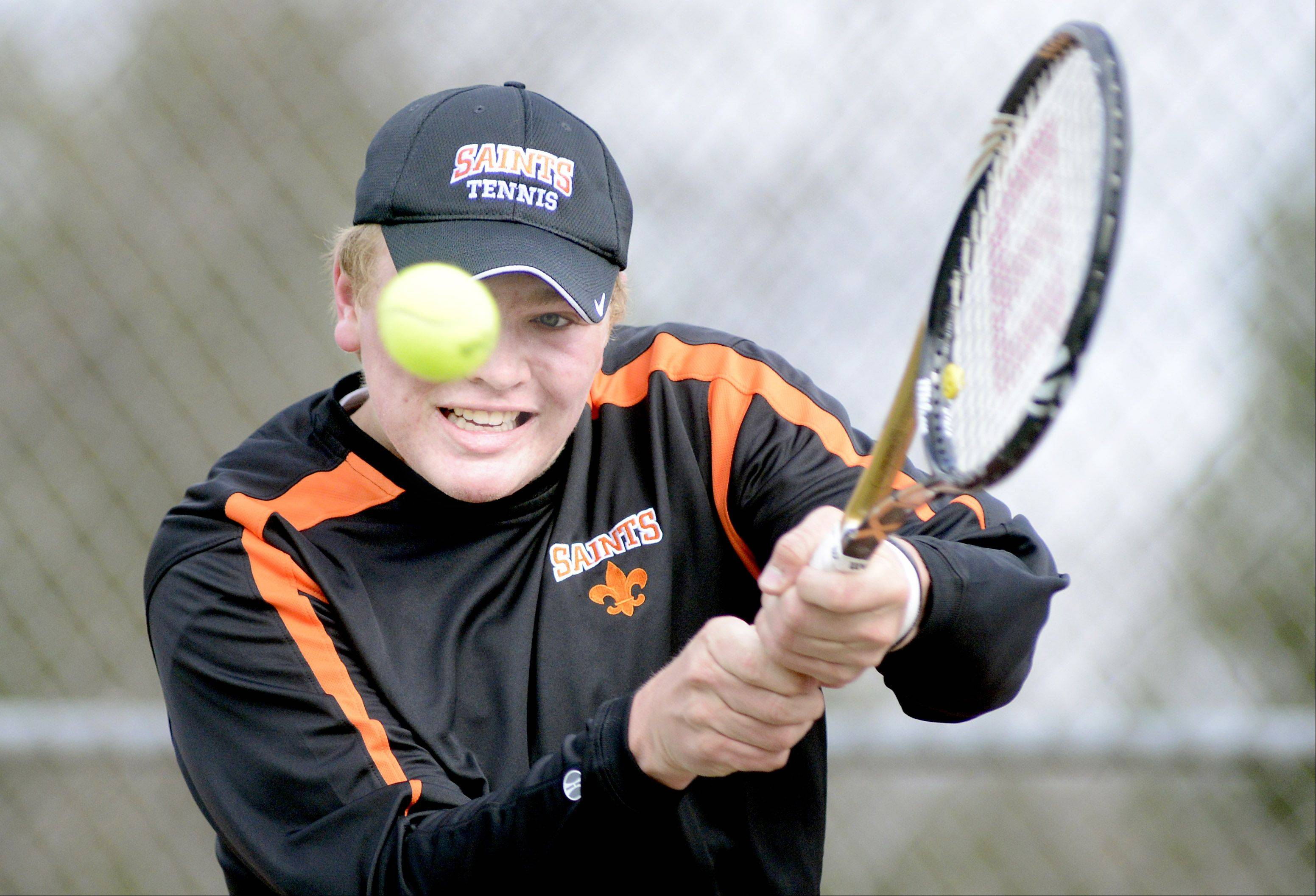 St. Charles East's Jasper Keenen returns a serve from IMSA on Saturday.