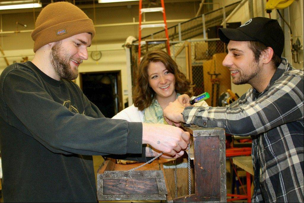 Harper student Paul Fritz of Arlington Heights, left, graduate Victoria Claus of Arlington Heights and student Nick Kohler of Elk Grove Village work on one of their latest furniture rehab projects: an old trunk-turned-mini bar.