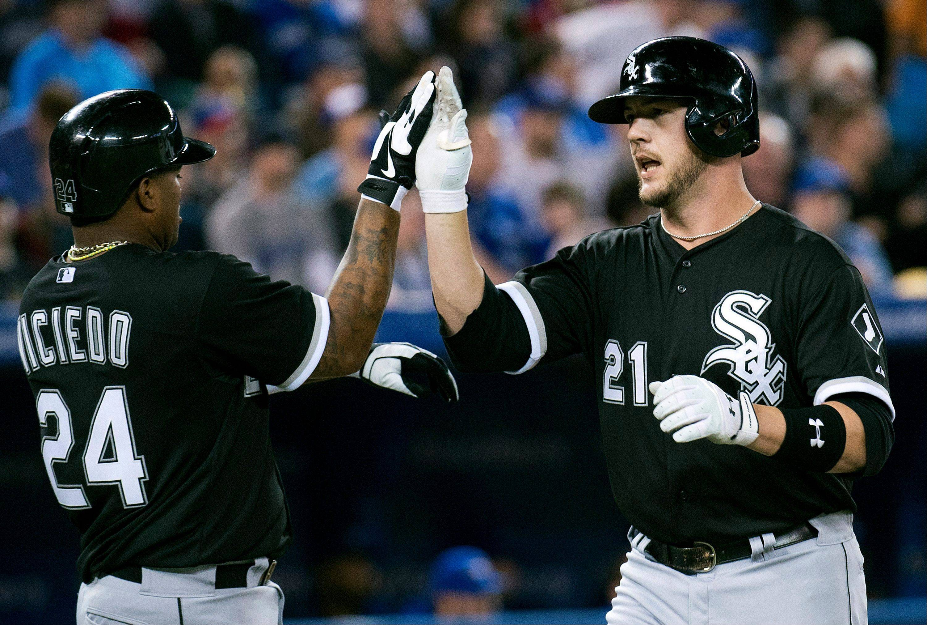 Chicago White Sox catcher Tyler Flowers, right, celebrates his three-run home run with teammate Dayan Viciedo, left, during the second inning of a baseball game in Toronto on Wednesday April 17, 2013.