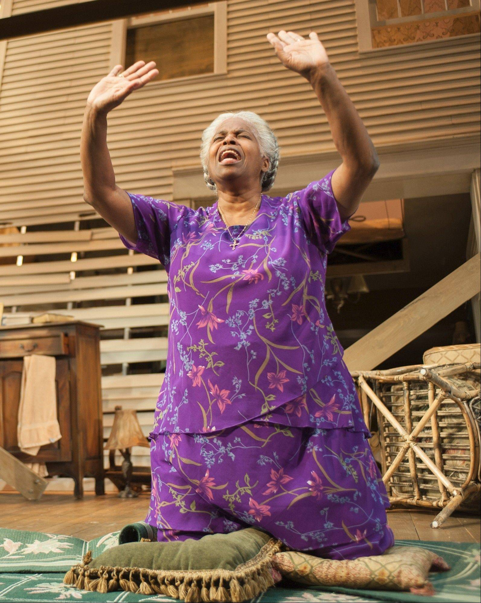 "Shelah (Cheryl Lynn Bruce) gets down on her knees in prayer in Steppenwolf Theatre Company's production of ""Head of Passes"" by ensemble member Tarell Alvin McCraney."