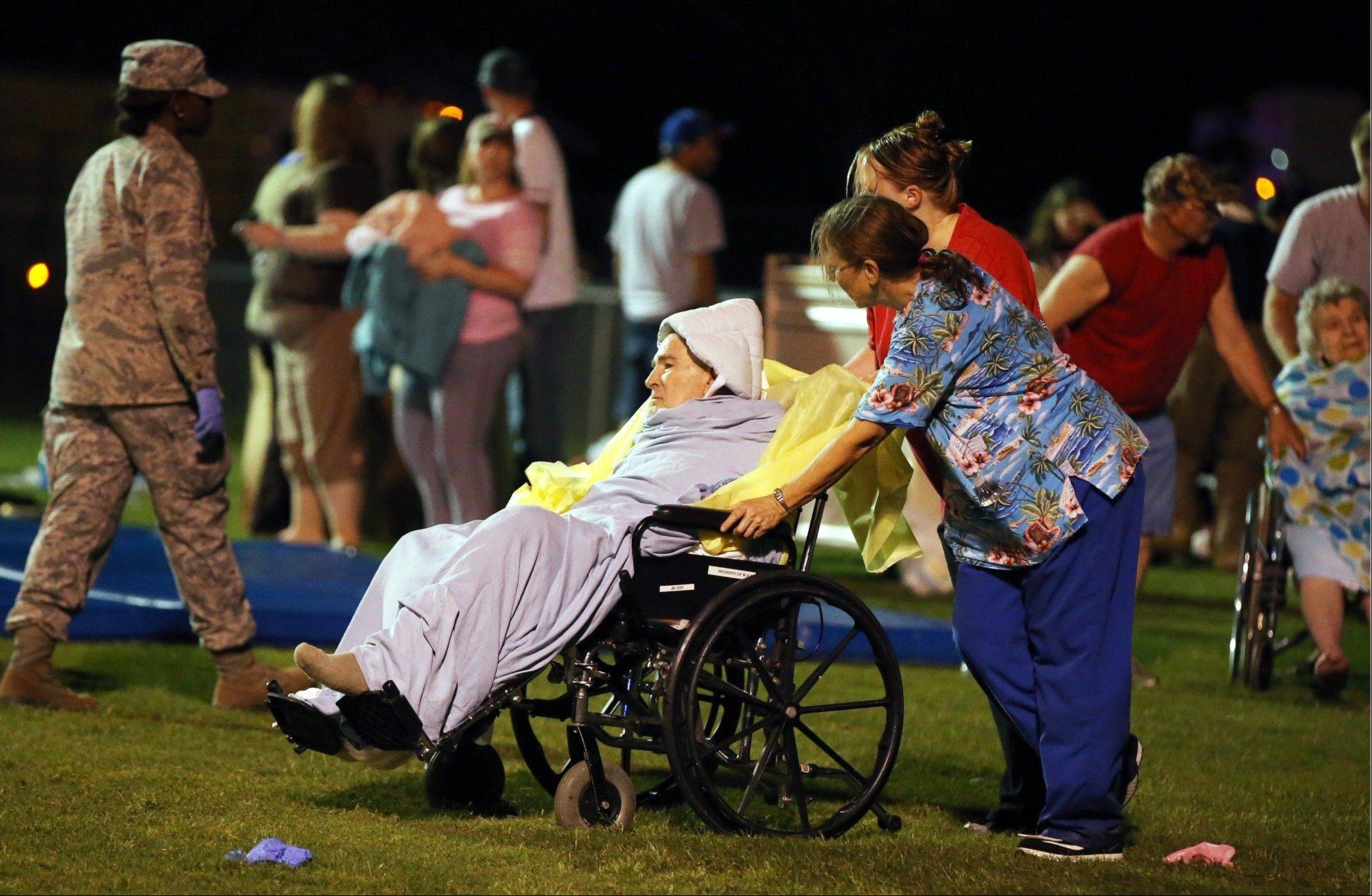 Emergency workers assist an elderly person at a staging area at a local school stadium Wednesday in West, Texas. An explosion Wednesday night at a fertilizer plant near Waco sent flames shooting high into the night sky, leaving the factory a smoldering ruin, causing major damage at nearby buildings and injuring numerous people.