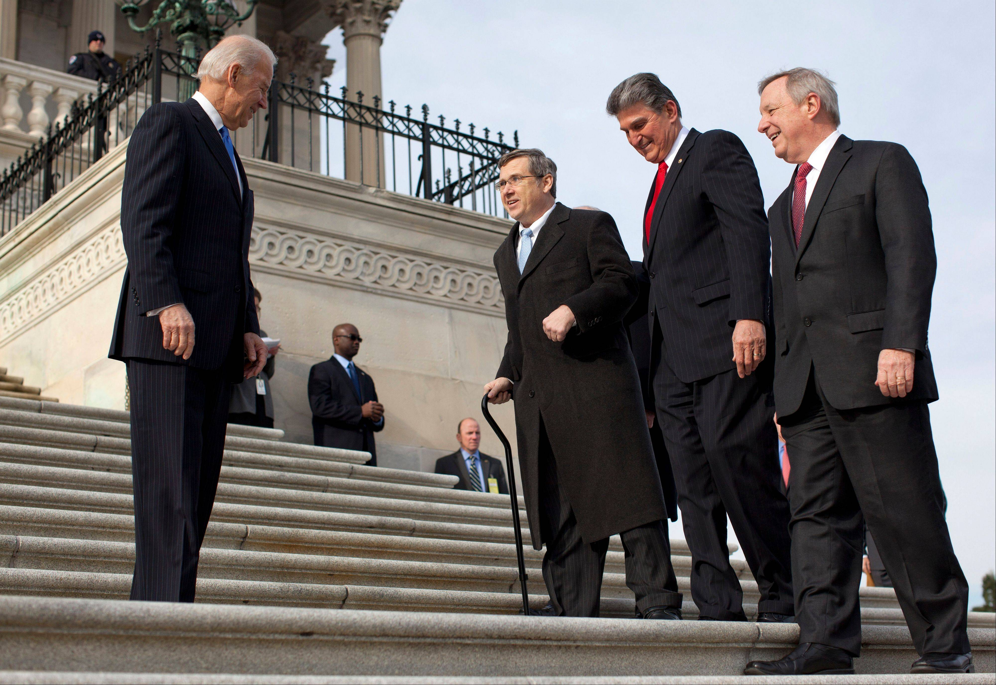 Vice President Joe Biden watches at left as Sen. Mark Kirk, second from left, accompanied by Sen. Joe Manchin, a West Virginia Democrat, second form right, and Senate Majority whip Dick Durbin, right, walks the steps to the Senate door of the Capitol building on Capitol Hill in Washington on Jan. 3, 2013. Manchin also said that Kirk, who voted Wednesday for in favor of expanded background checks on gun buyers, held steadfast to closing all loopholes at gun shows, a point of contention among some other Republicans.