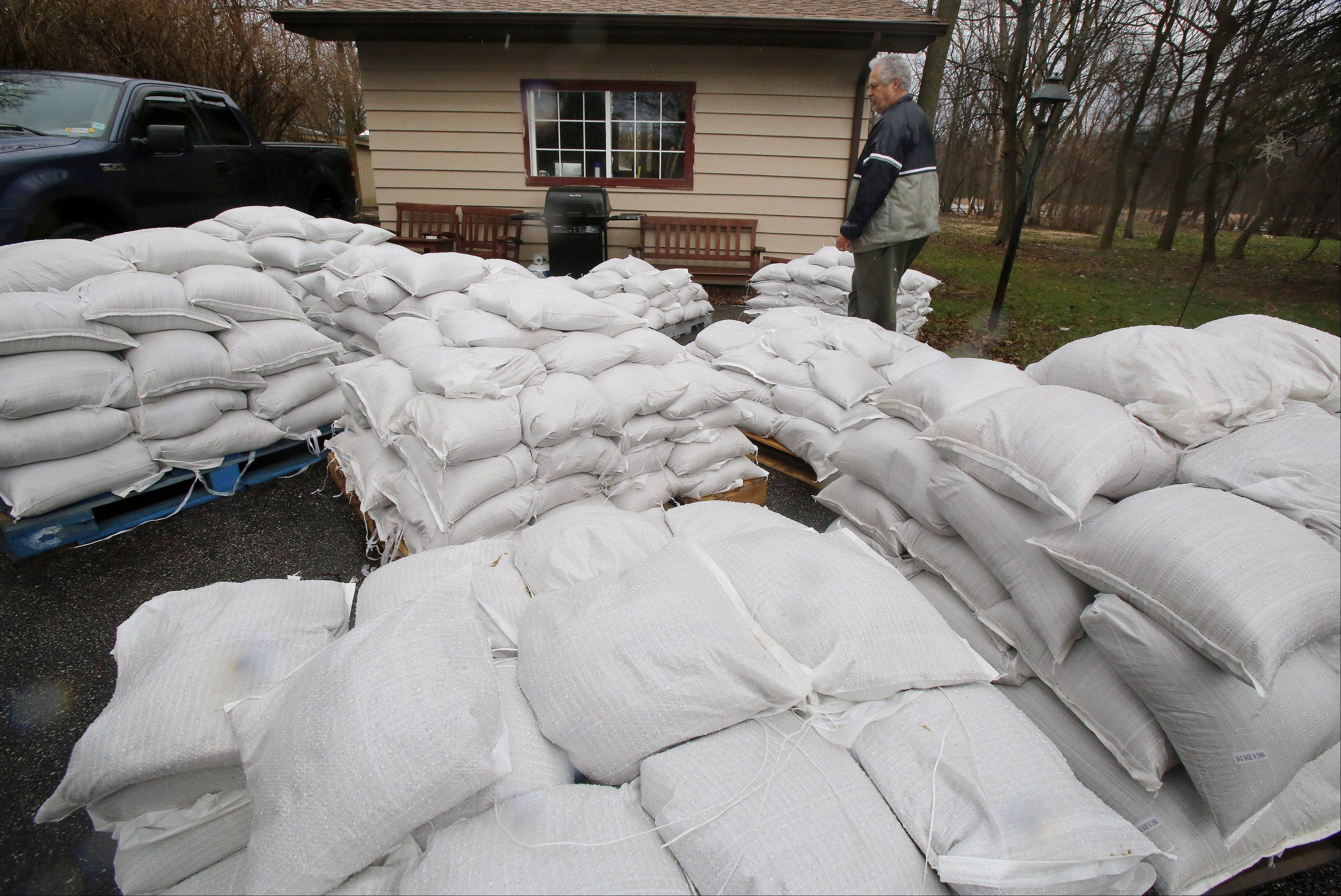 Gurnee resident Carl Marro walks around the pallets of sandbags delivered to his house along the Des Plaines River by Gurnee Public Works crews Wednesday. Volunteers filled sandbags in Gurnee as heavy rains are expected to continue Thursday.