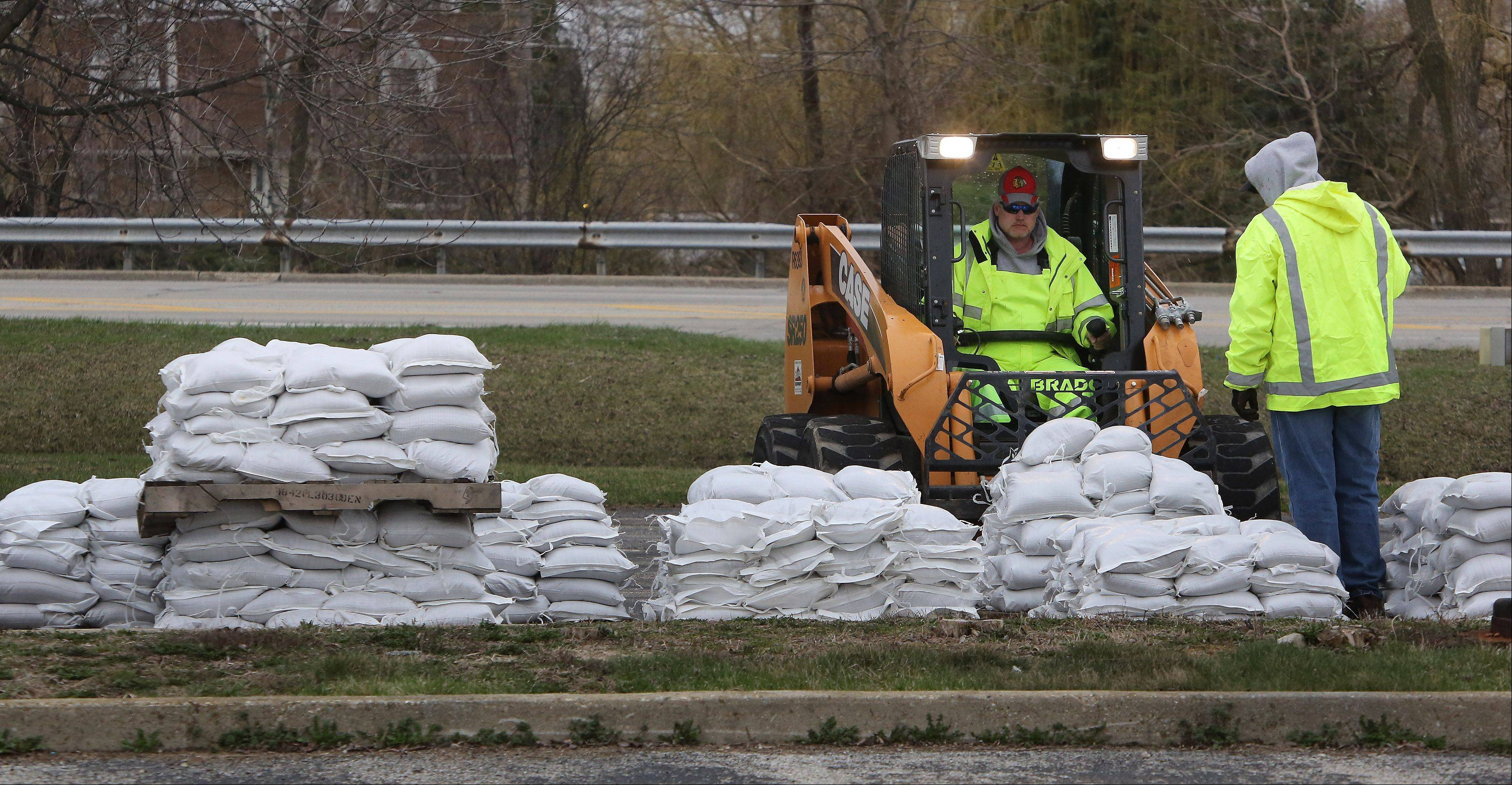 Gurnee Public Works employees Brian Walsh, left, and Dave Zirbel move pallets of sandbags Wednesday to help protect area residents and businesses from any Des Plaines River flooding.