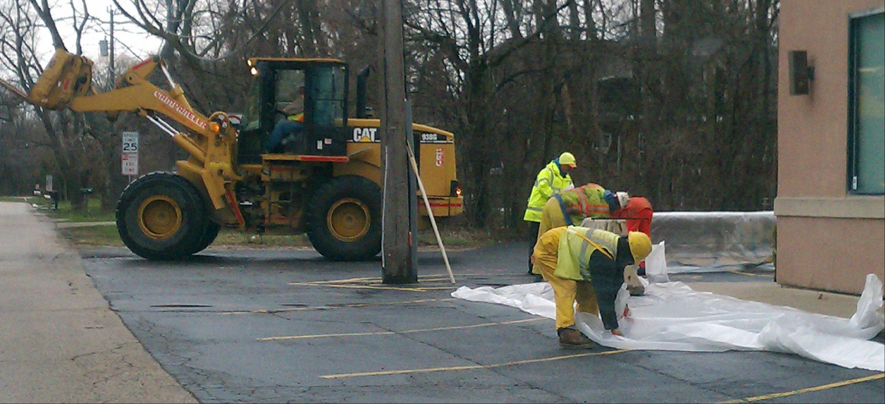 Workers prepare for floods on Old Grand Avenue in Gurnee Wednesday.