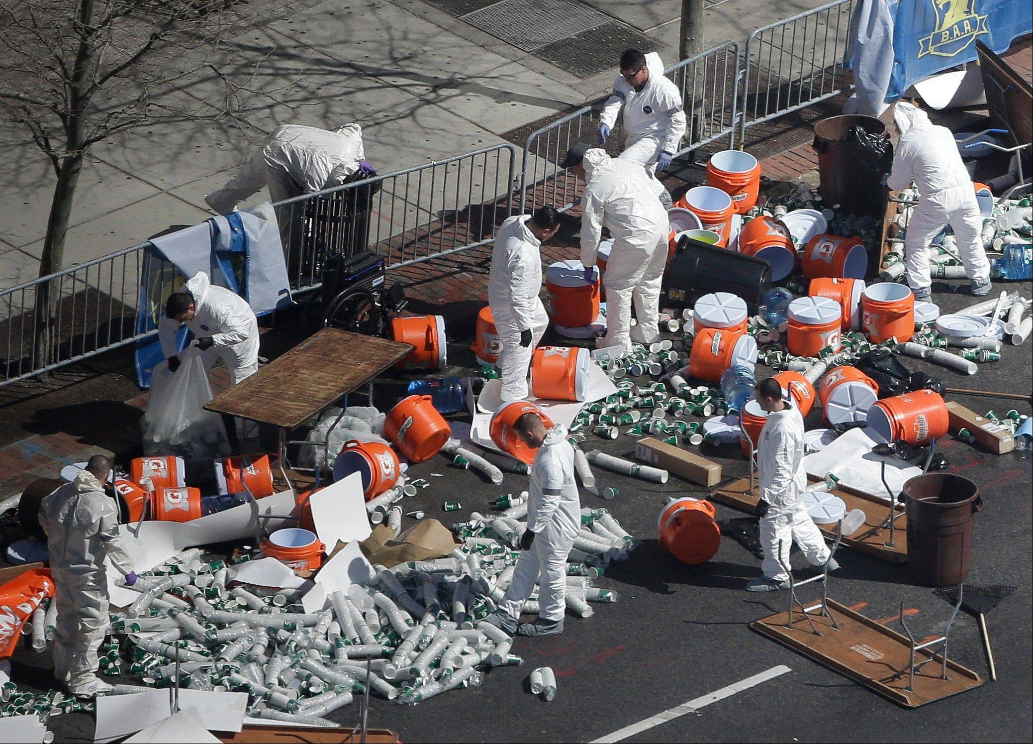 Investigators comb through the post finish line area of the Boston Marathon at Boylston Street, two days after two bombs exploded just before the finish line, Wednesday.
