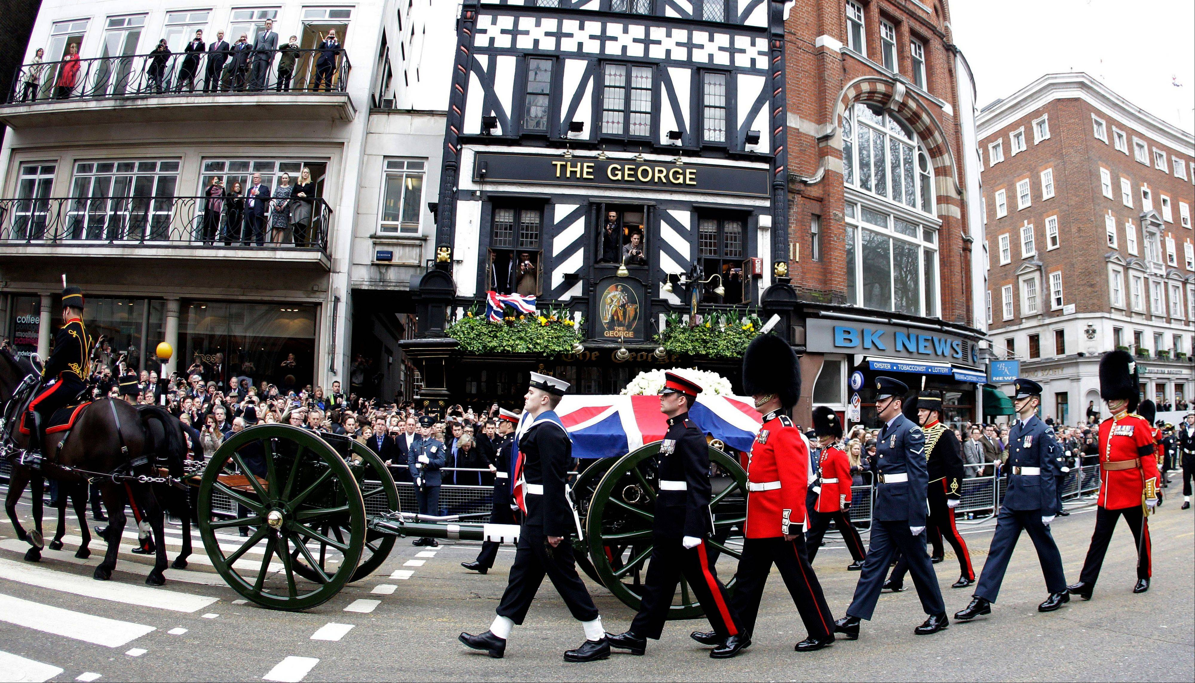 In this photo taken with a fisheye lens, a Union flag draped coffin bearing the body of former British Prime Minister Margaret Thatcher is carried on a gun carriage drawn by the King's Troop Royal Artillery during her ceremonial funeral procession in London, Wednesday, April 17, 2013. The Iron Lady is being laid to rest -- yet even in death, she remains a divisive figure.