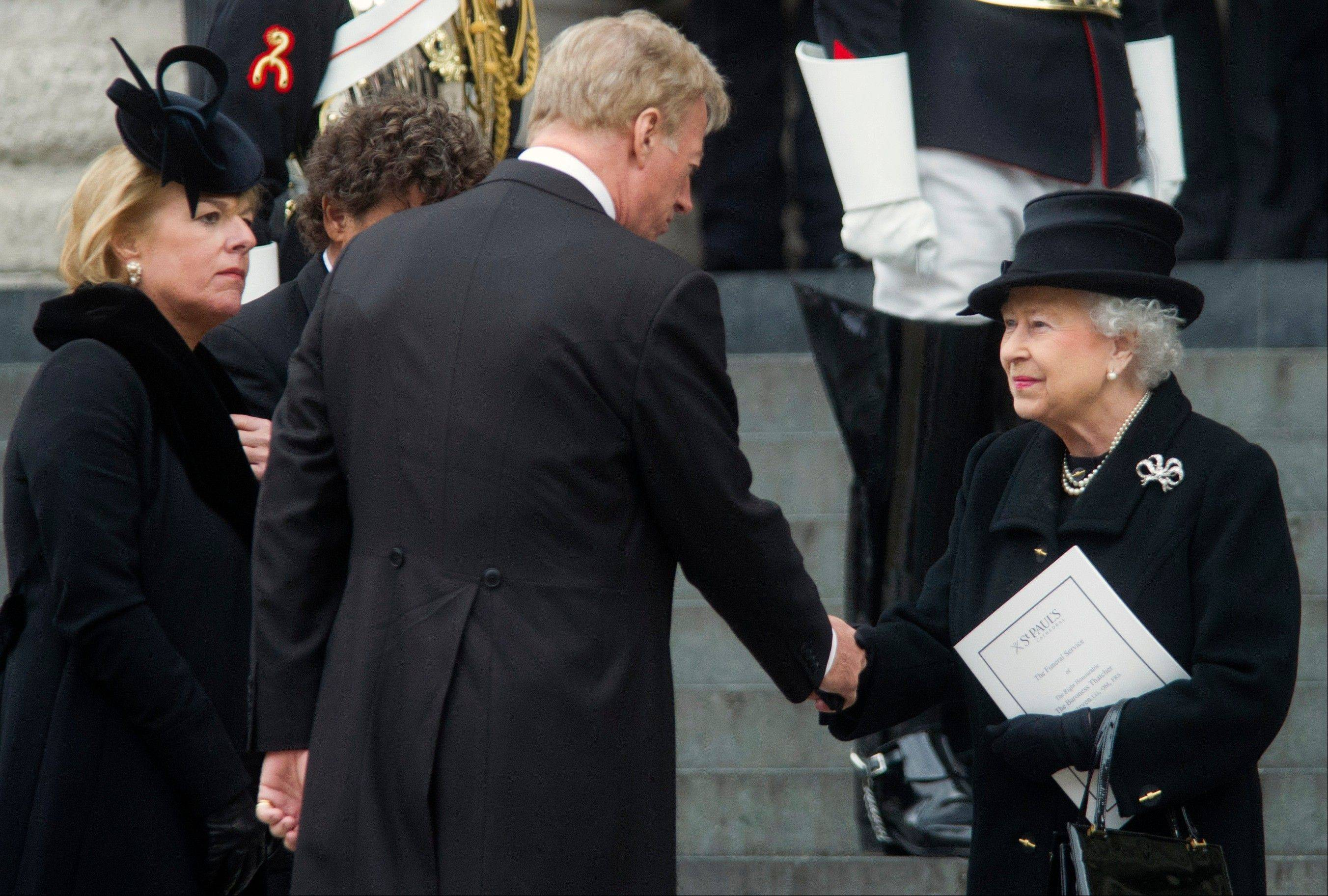 Carol Thatcher, left, the daughter of former British Prime Minister Margaret Thatcher looks on as her brother Mark Thatcher, center, shakes hands with Britain's Queen Elizabeth II, following the former prime minister's funeral ceremony at St. Paul's Cathedral, London, Wednesday, April 17, 2013. Margaret Thatcher, Britain's Iron Lady, was laid to rest Wednesday with a level of pomp and protest reflecting her status as a commanding, polarizing political figure.