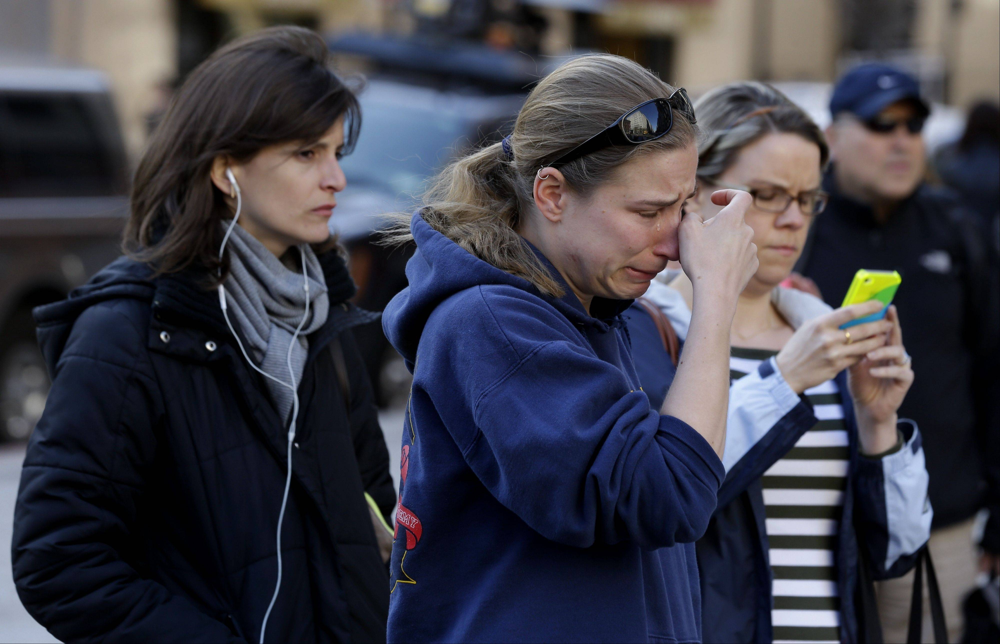 Jillian Blenis, 30, center, of Boston, reacts while stopping at a makeshift memorial, Wednesday, April 17, 2013, in Boston. The city continues to cope following Monday's explosions near the finish line of the Boston Marathon.