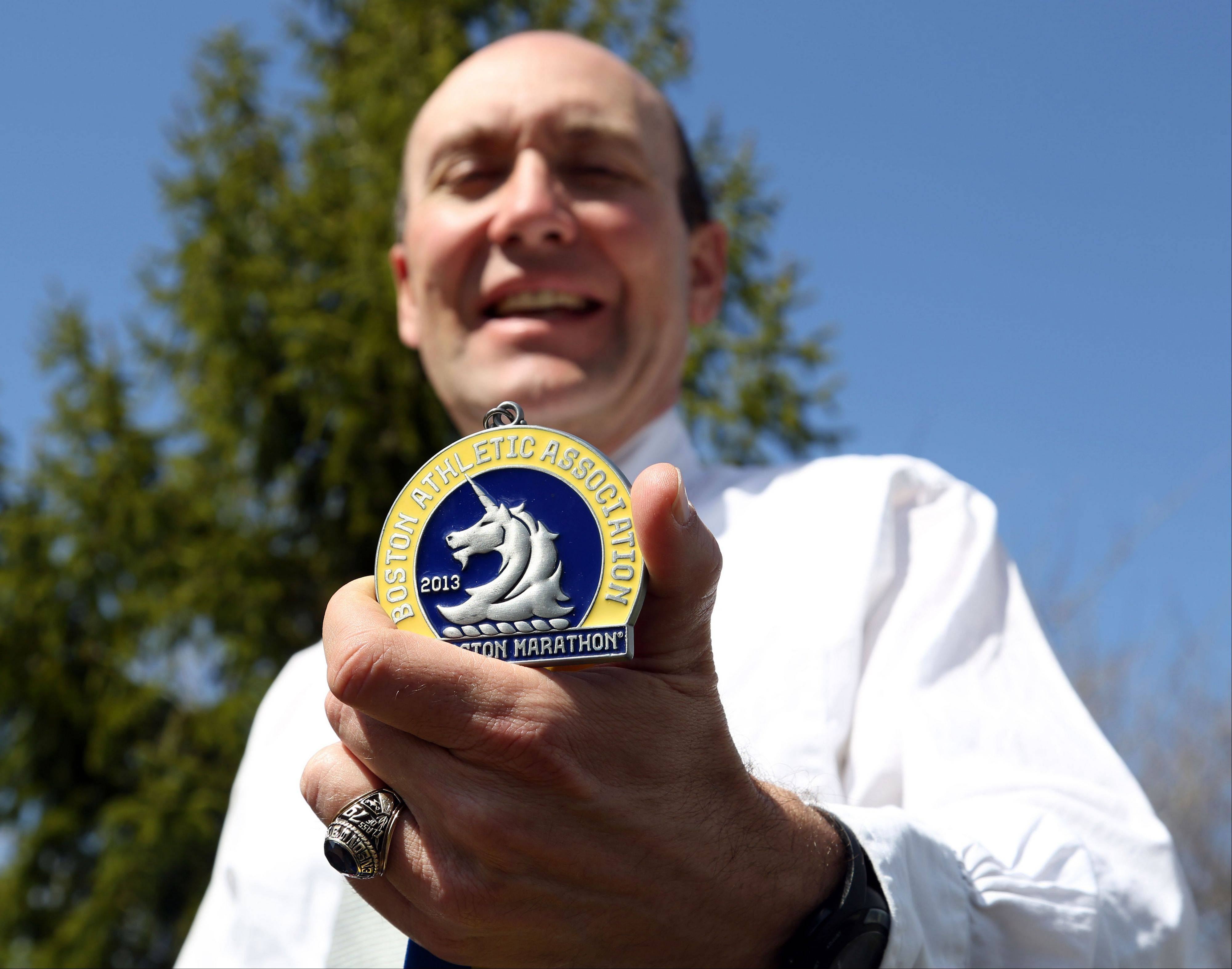 Hawthorn Woods resident Al Scaletta holds up his medallion from Monday's Boston Marathon. He plans to run the Boston Marathon again next year.