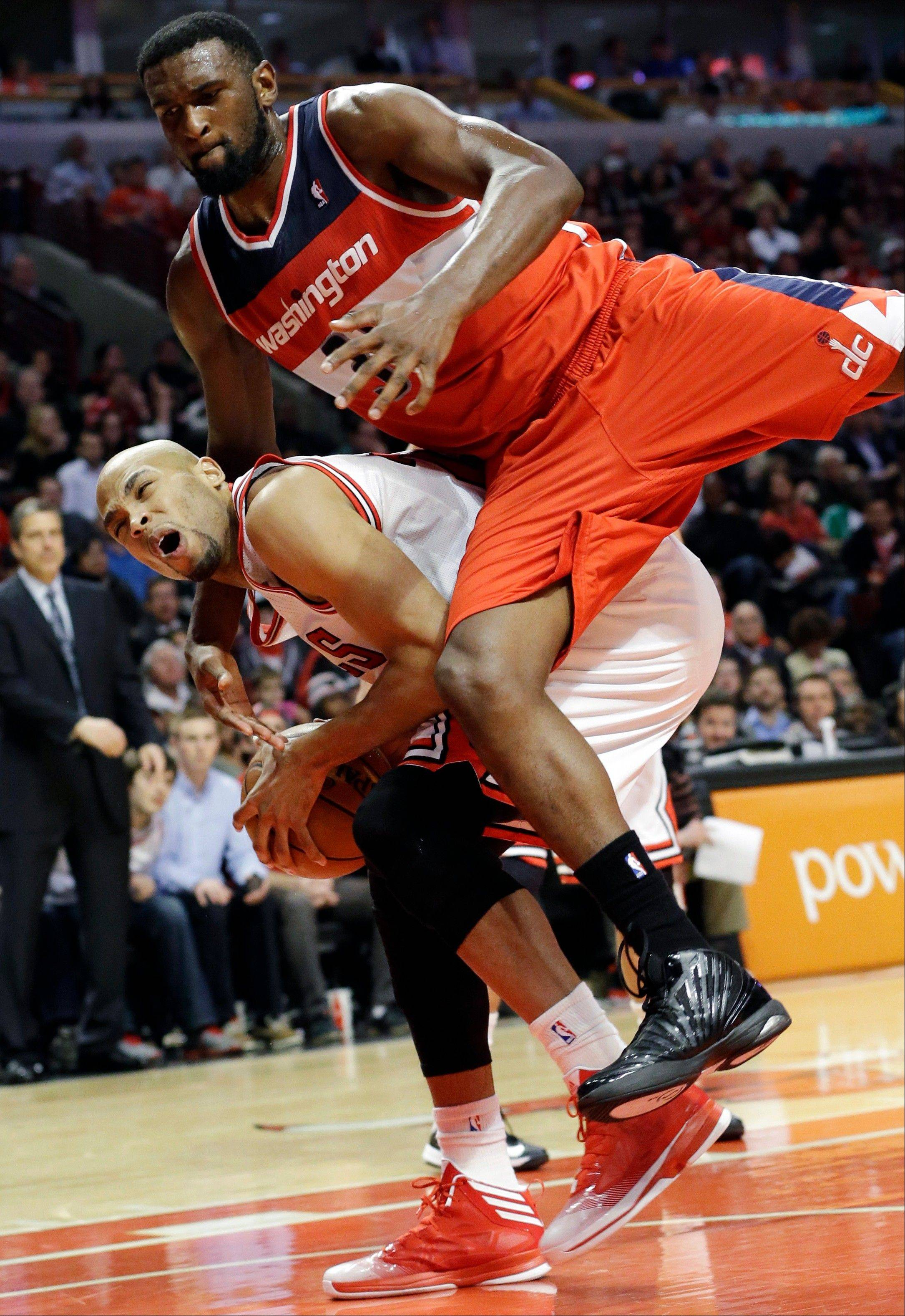 Washington Wizards forward Chris Sigleton, top, fouls Chicago Bulls forward Taj Gibson during the second half of an NBA basketball game in Chicago, Wednesday, April 17, 2013. The Bulls won 95-92.
