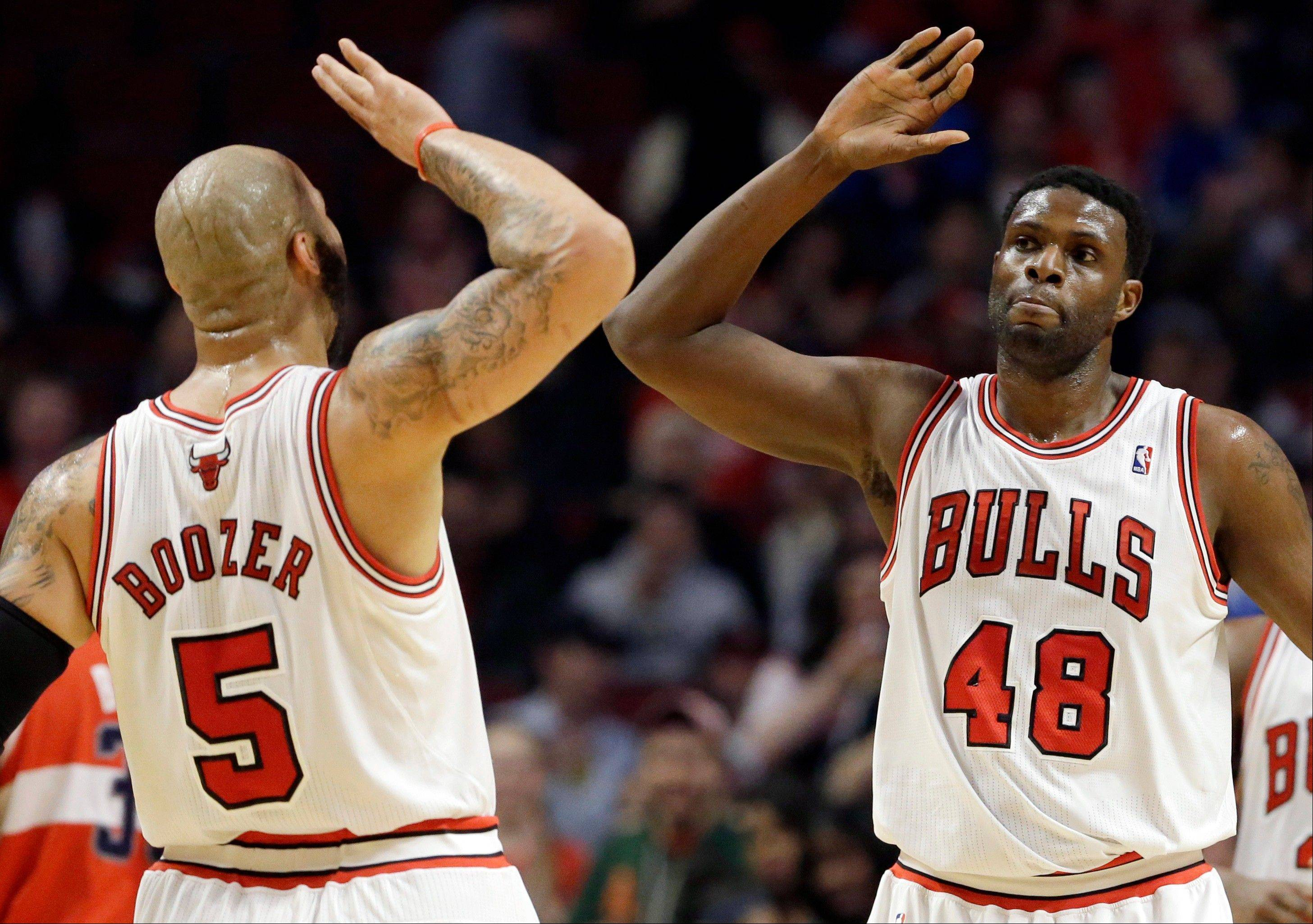 Chicago Bulls center Nazr Mohammed, right, celebrates with forward Carlos Boozer after scoring a basket during the first half of an NBA basketball game against the Washington Wizards in Chicago, Wednesday, April 17, 2013.