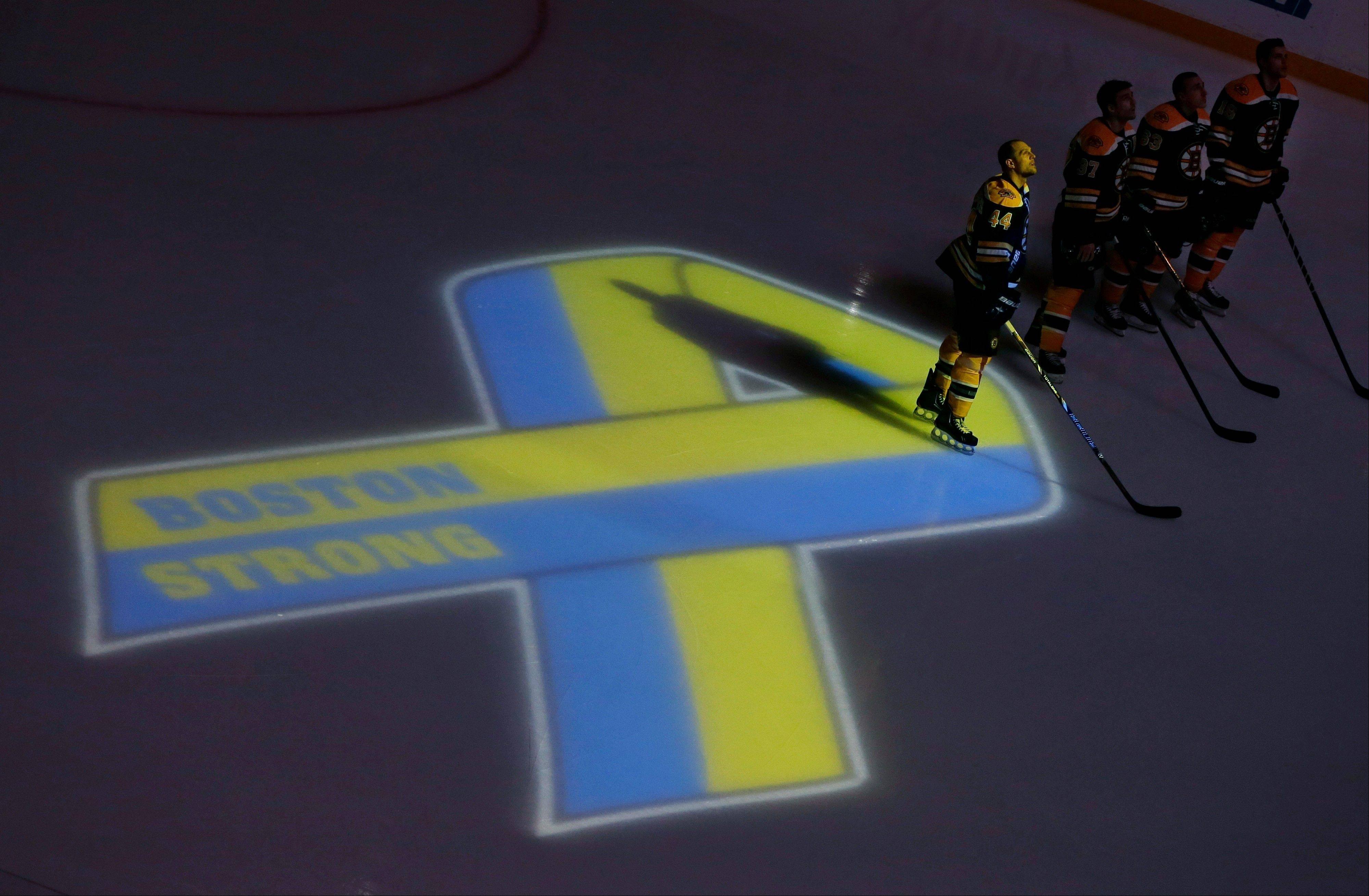 Boston Bruins hockey starters, including defenseman Dennis Seidenberg (44), stand next to a ribbon projected onto the ice at TD Garden in Boston, Wednesday, April 17, 2013, during a pregame ceremony in the aftermath of Monday's Boston Marathon bombings.