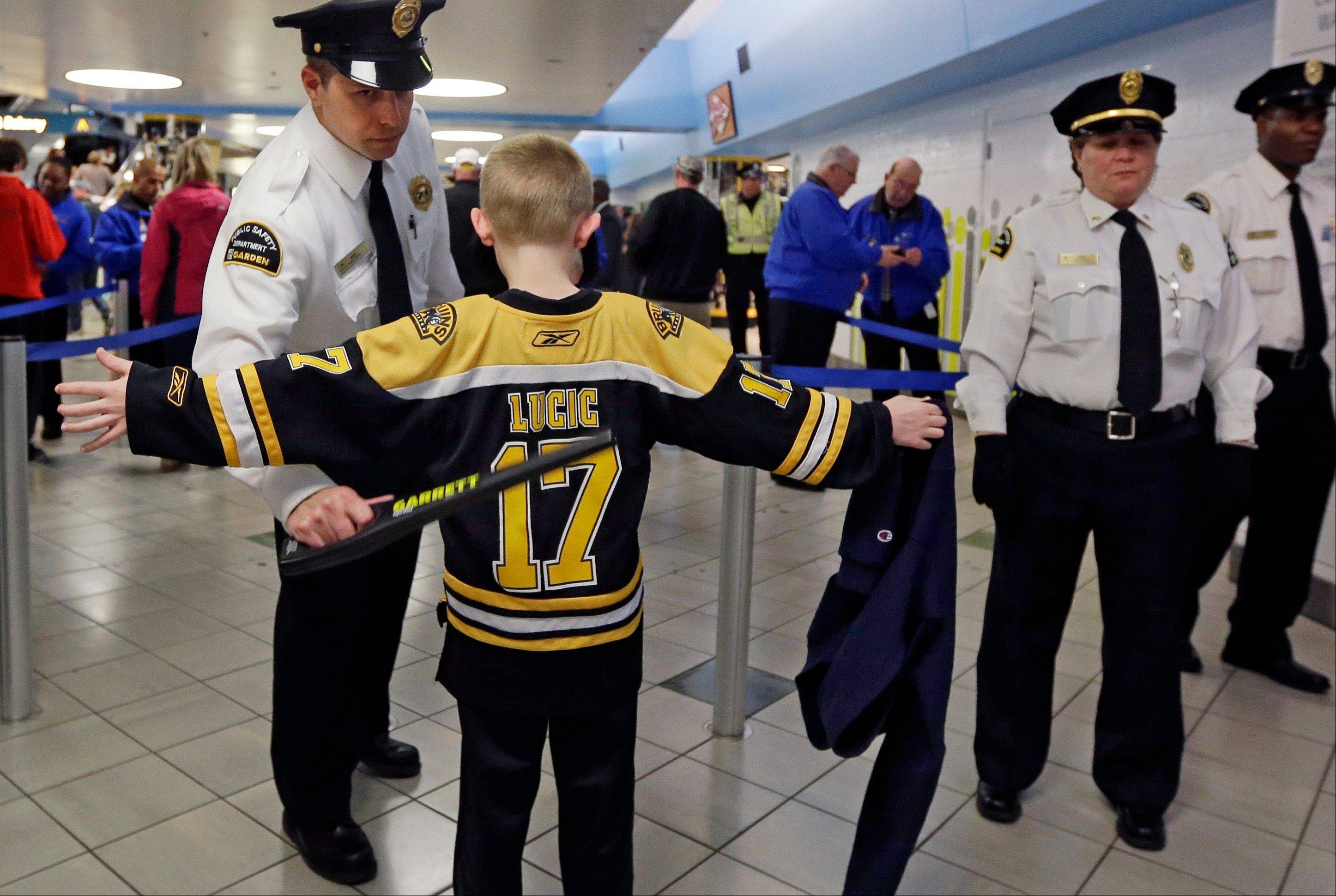 A young Boston Bruins fan raises his arms to be checked on the way into TD Garden prior to a Bruins NHL hockey game against the Buffalo Sabres in Boston, Wednesday, April 17, 2013, in the aftermath of Monday's Boston Marathon bombings.