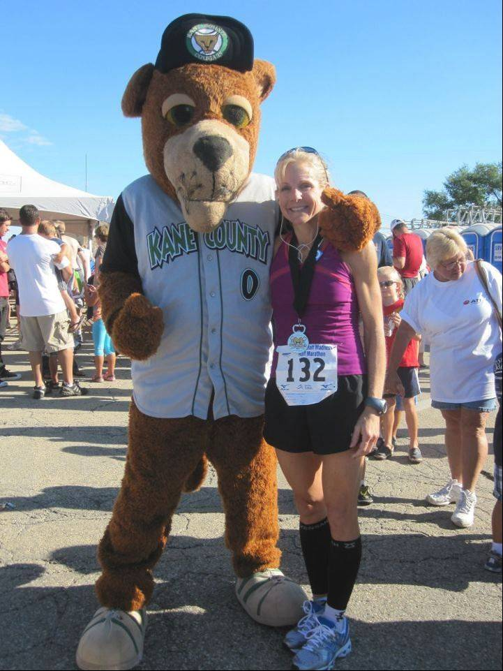 Elgin resident Sue Gruner, right, poses with Ozzie the Cougar after completing the Fox Valley Marathon last year.