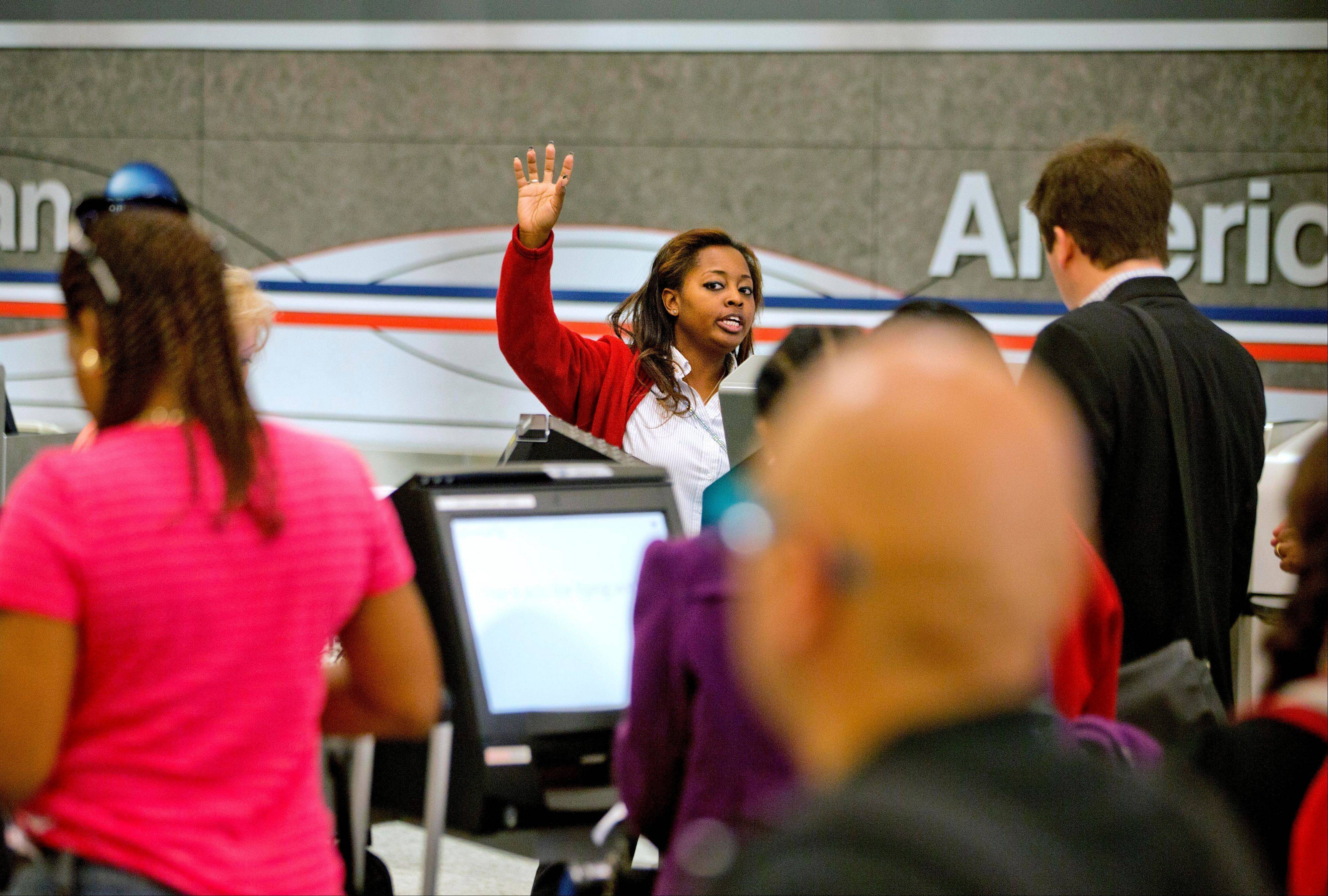 The parent of American Airlines is reporting a smaller loss for the first quarter than a year ago on slightly higher revenue and much lower labor costs.
