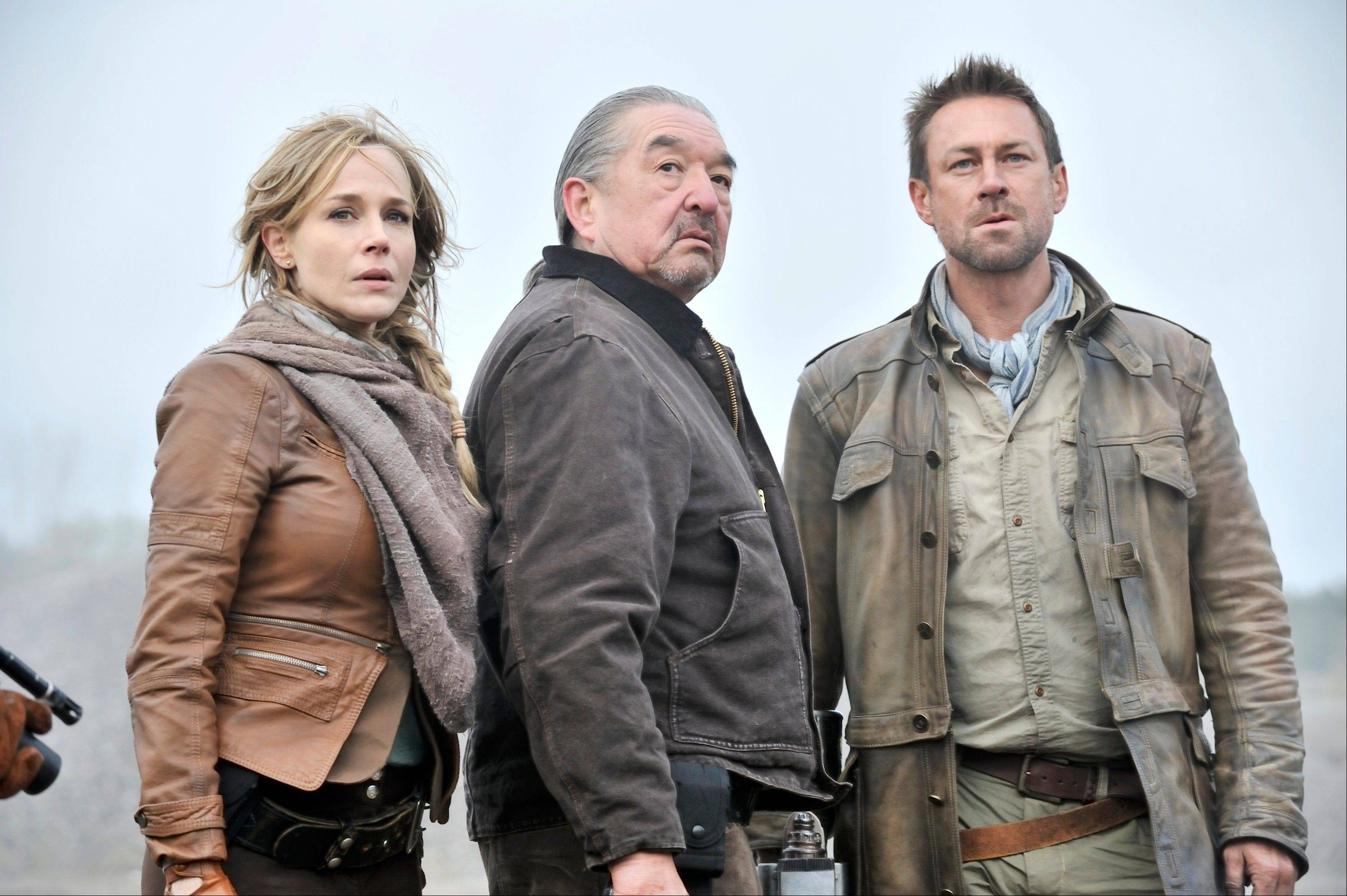 "Julie Benz plays Amanda Rosewater, left, Graham Greene as Rafe McCawley, and Grant Bowler as Jeb Nolan, in the new series ""Defiance"" on Syfy."
