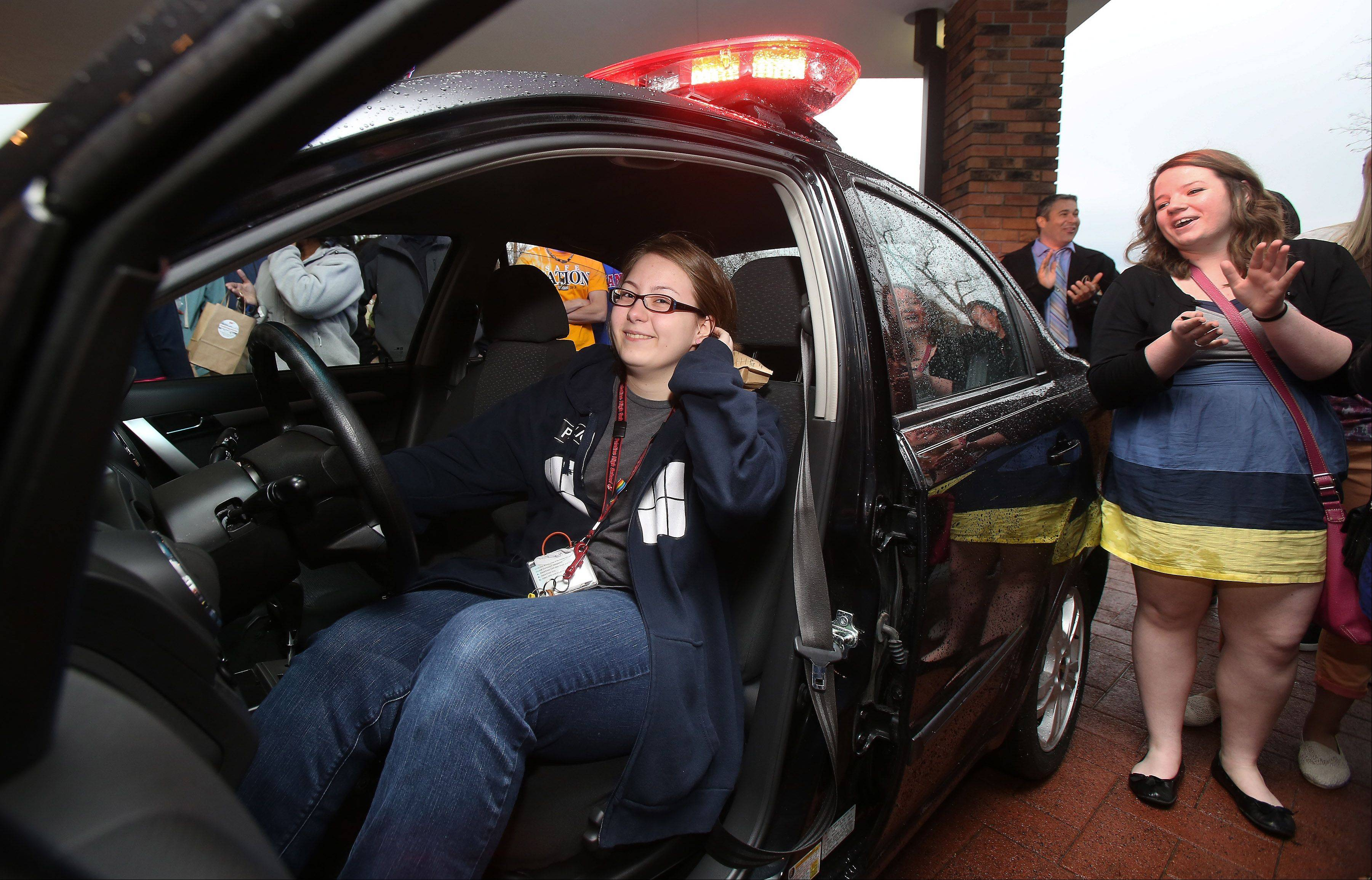 Palatine High School sophomore Emina Mesic turns a key and wins a car during an Operation Click luncheon Wednesday in Kildeer. High school students took a pledge to drive safe for a chance to win a car. Mesic was the last student to try a key for the car.
