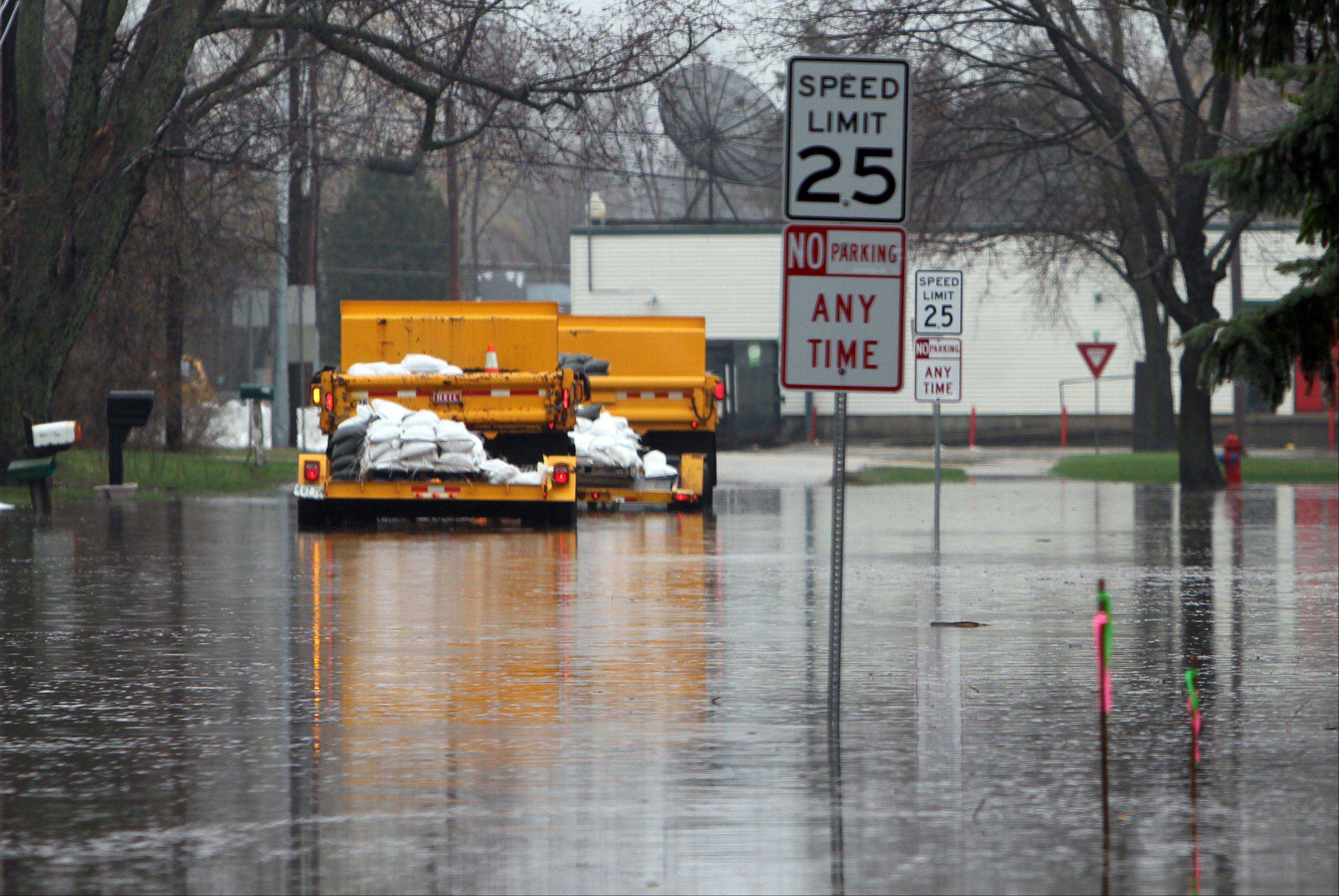 Trucks with sandbags head down flooded Emerald Avenue near Old Grand Avenue in Gurnee on Thursday morning.