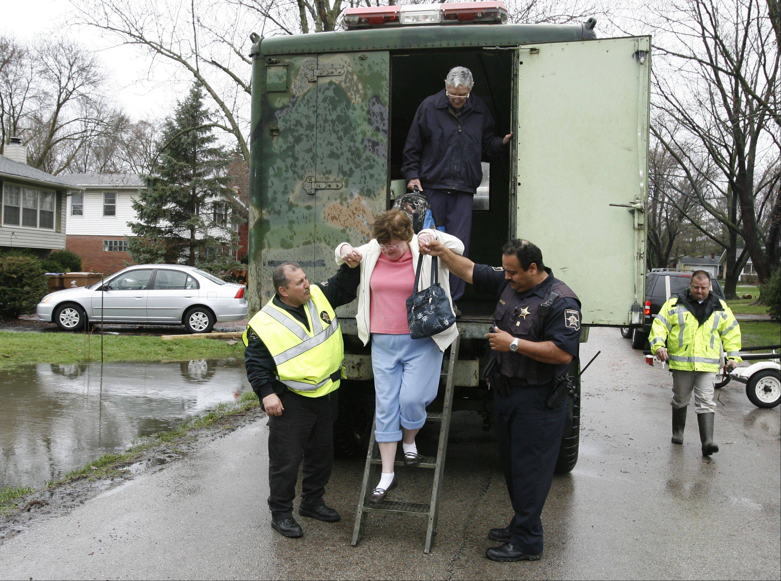 DuPage County sheriff's deputies assist a resident who was rescued from her flooded home in the Valley View subdivision near Glen Ellyn.