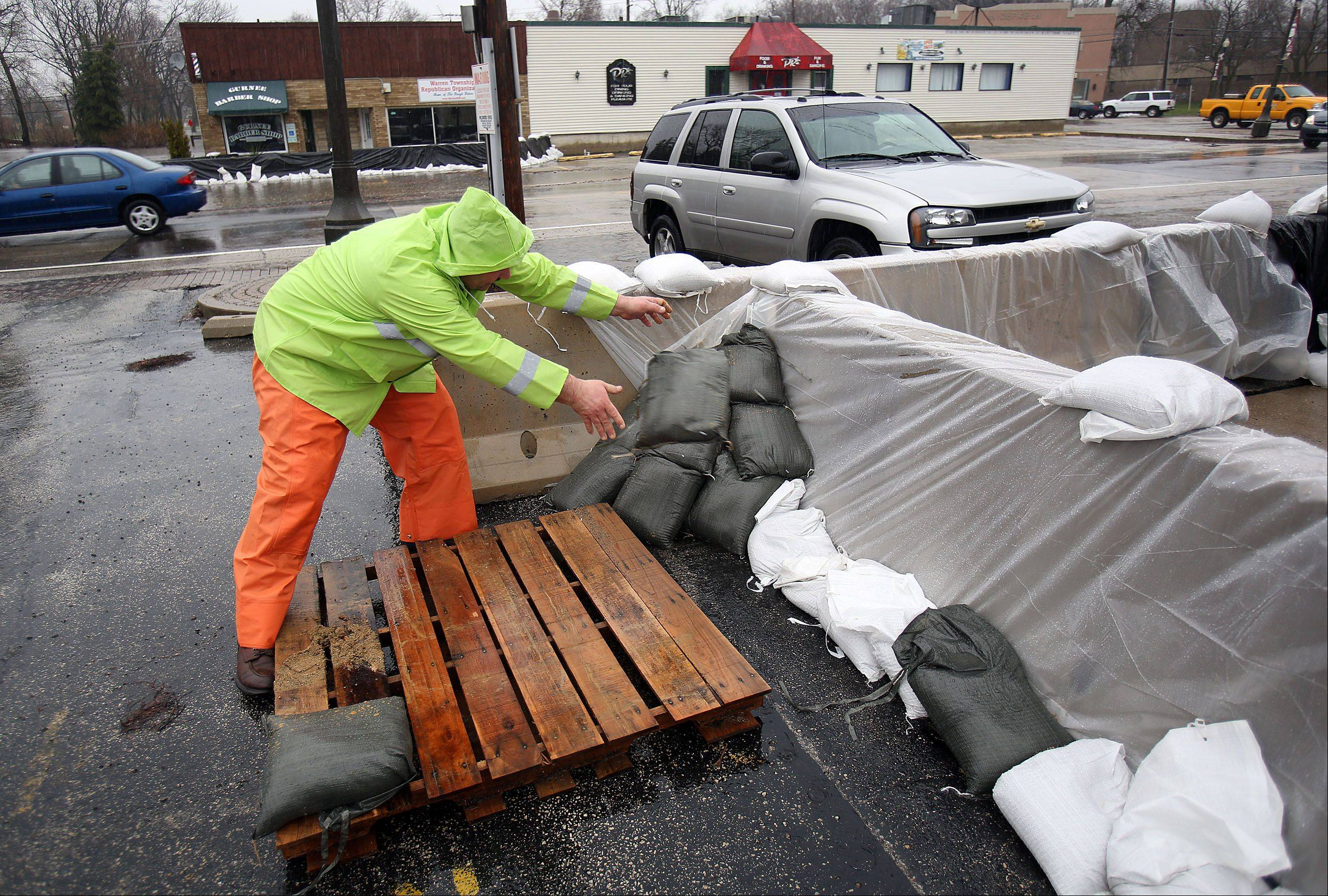 Steve Lundy/slundy@dailyherald.com Volunteer Fred Rickert of Zion places sandbags at Tranquility Salon on Old Grand Avenue in Gurnee Thursday morning.