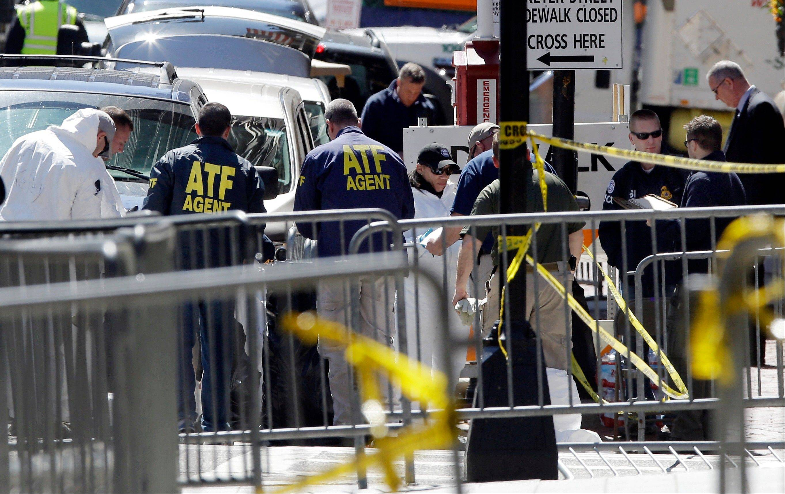 ATF agents and others examine an area of Boylston Street in Boston Thursday, April 18, 2013, as investigation of the Boston Marathon bombings continues.